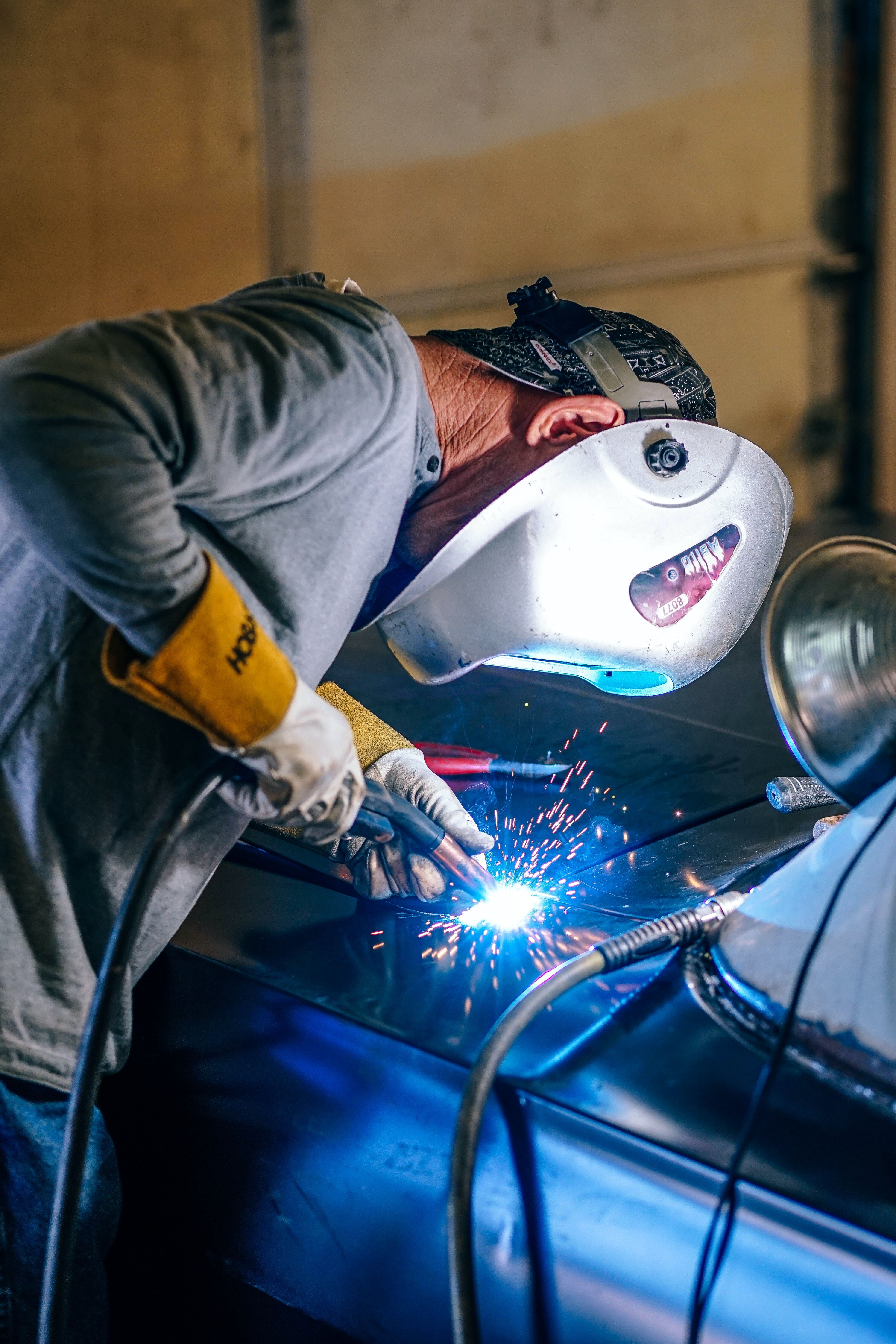 person with mask welding on vehicle