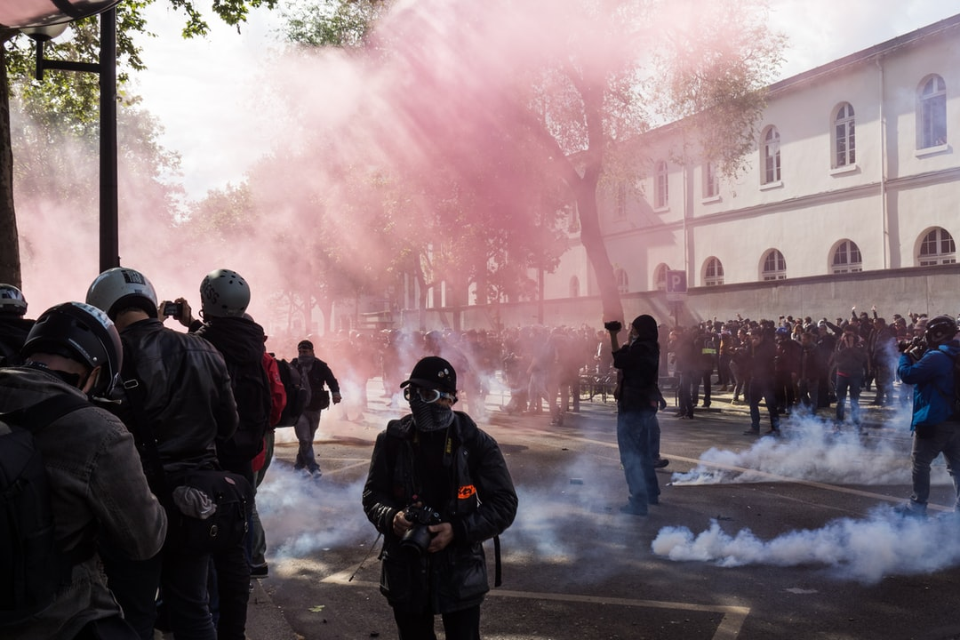 A pink smoke bomb and tears gaz during the protest of may 1st 2017, in Paris. A lot of protesters and journalists.