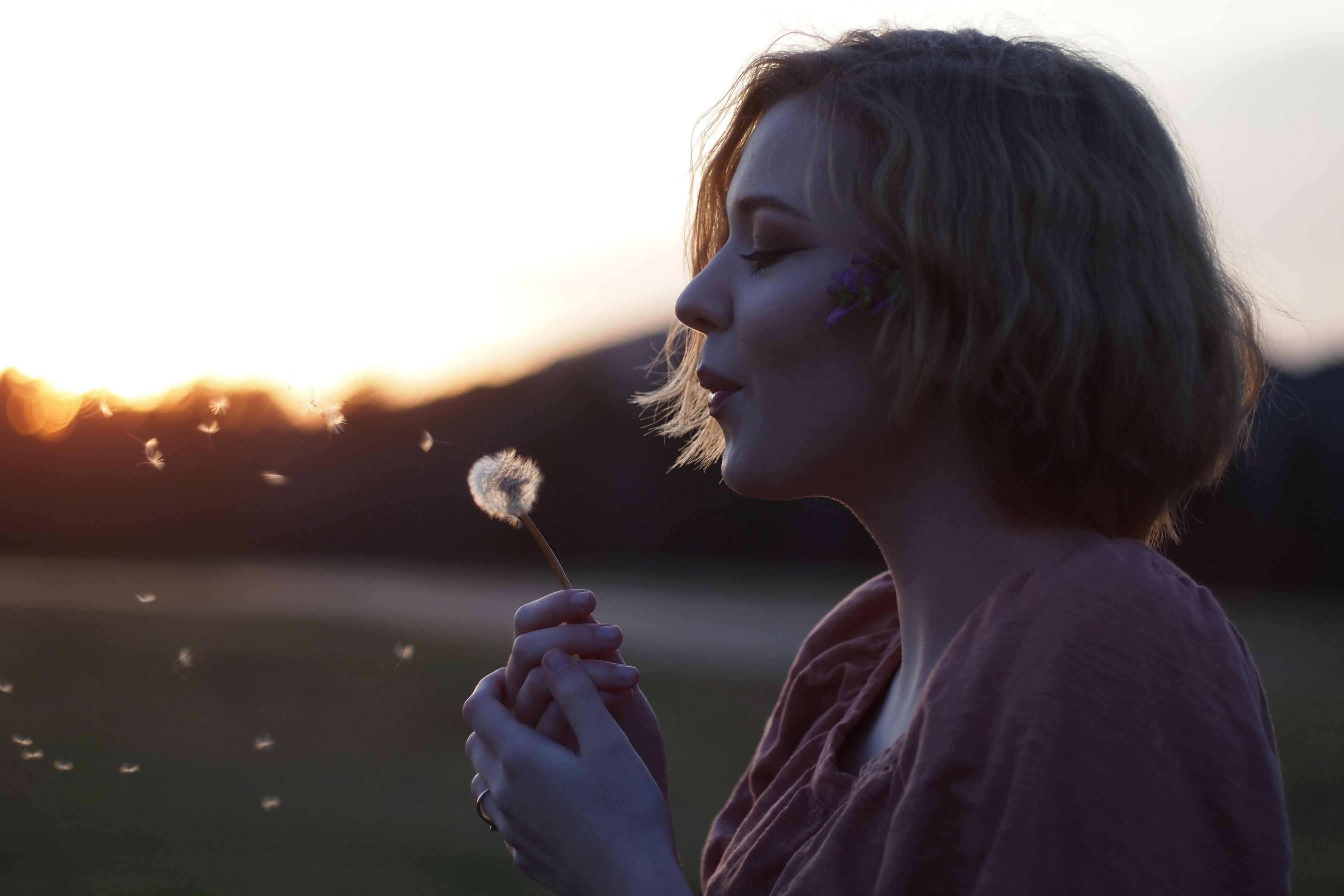 Woman blows dandelion seeds and makes a wish