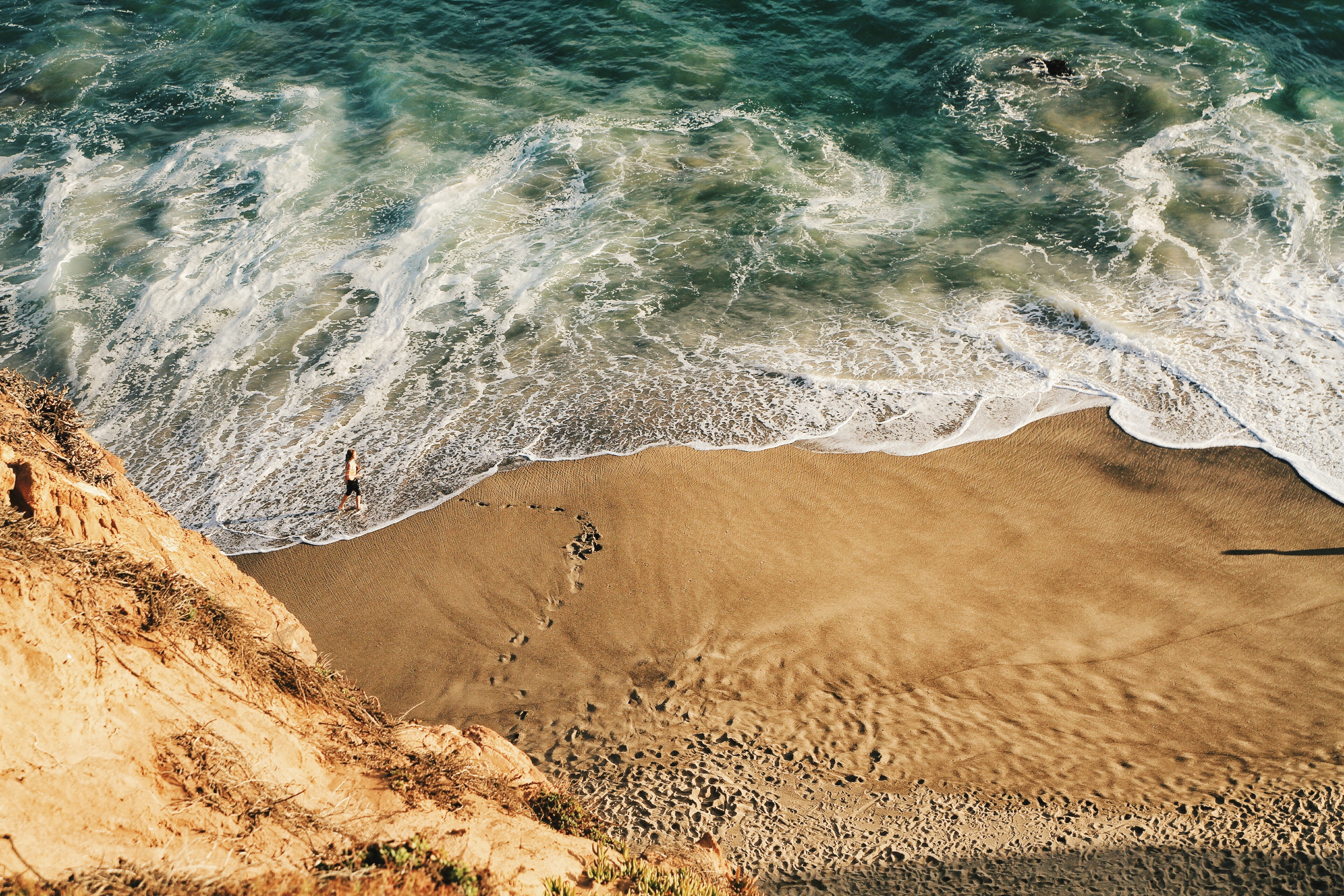 View from the cliff on a person walking down the sand beach by the foamy ocean waves