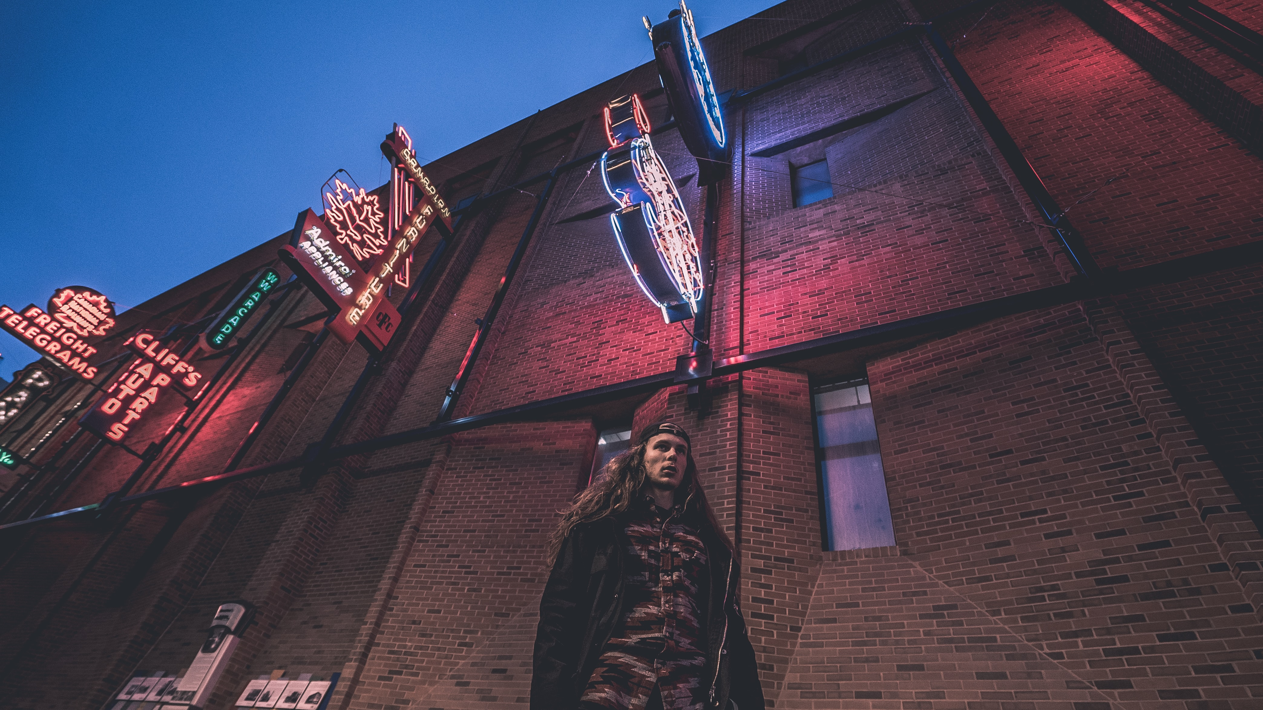 A man with long hair stands beneath neon signs at dusk in Edmonton