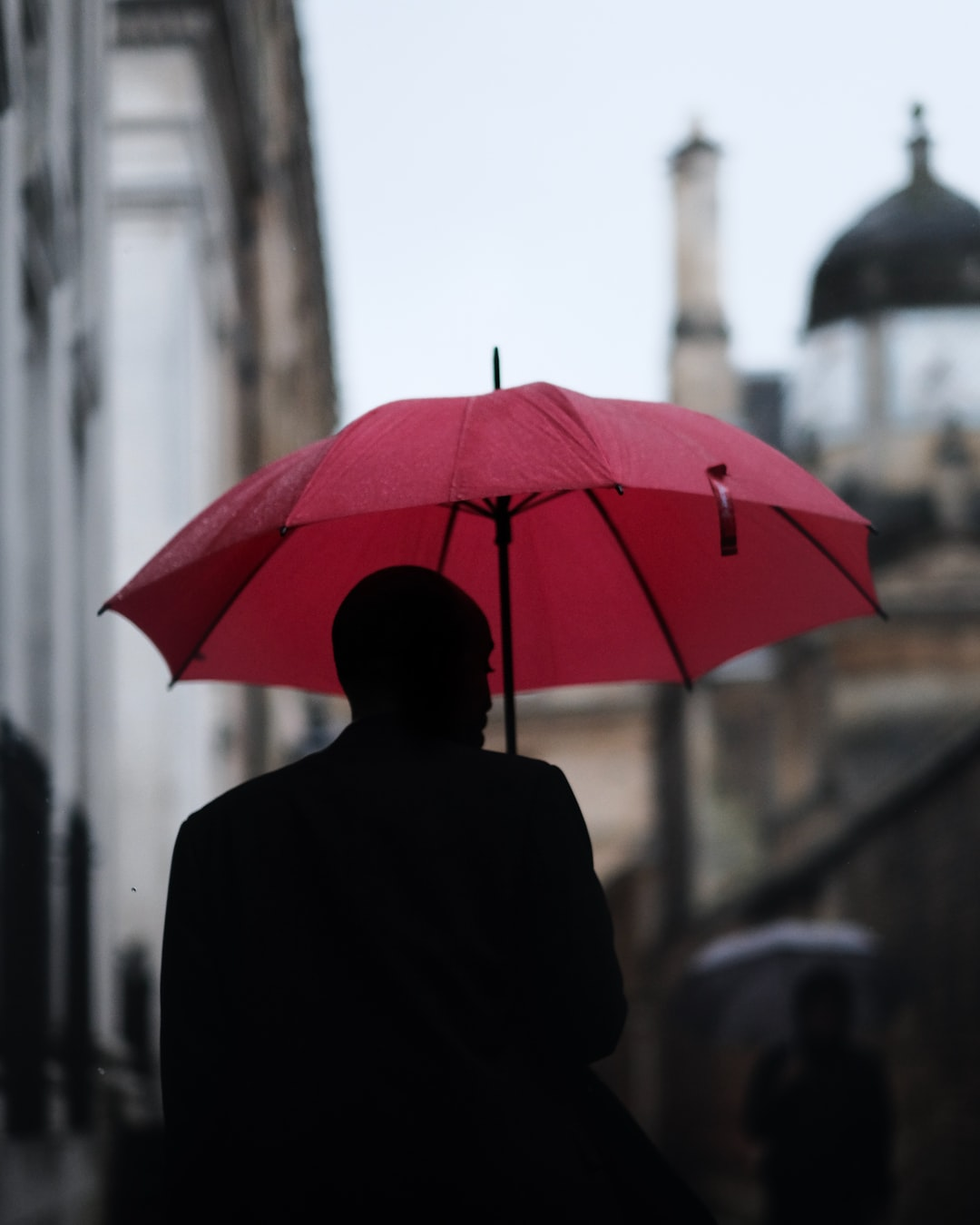 a man with a red umbrella disappears down senate house passage in cambridge uk