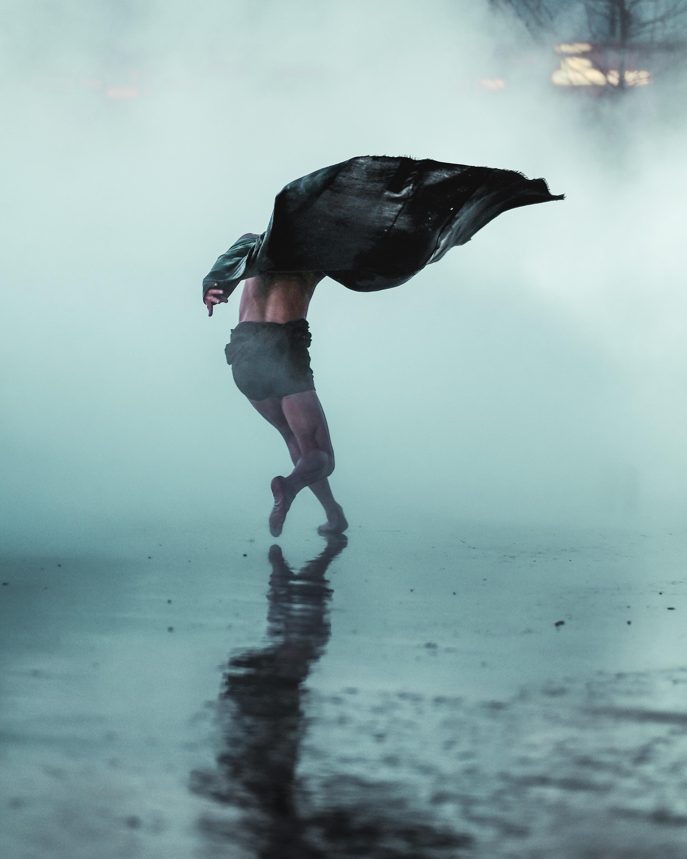 Man runs gracefully through fog and rain in Tate Modern