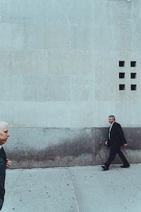 two man walking near building