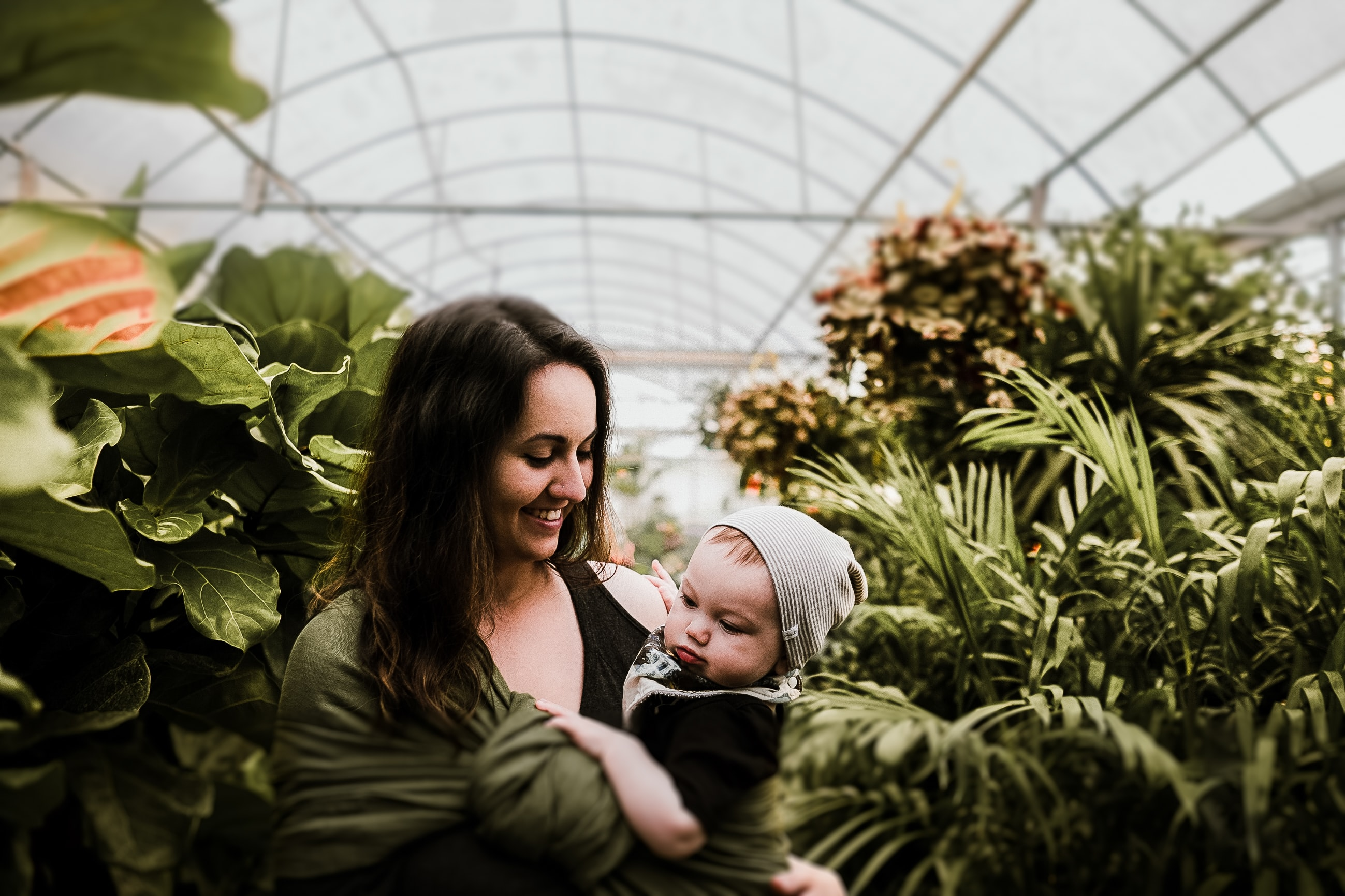 A mother holding her child in a greenhouse