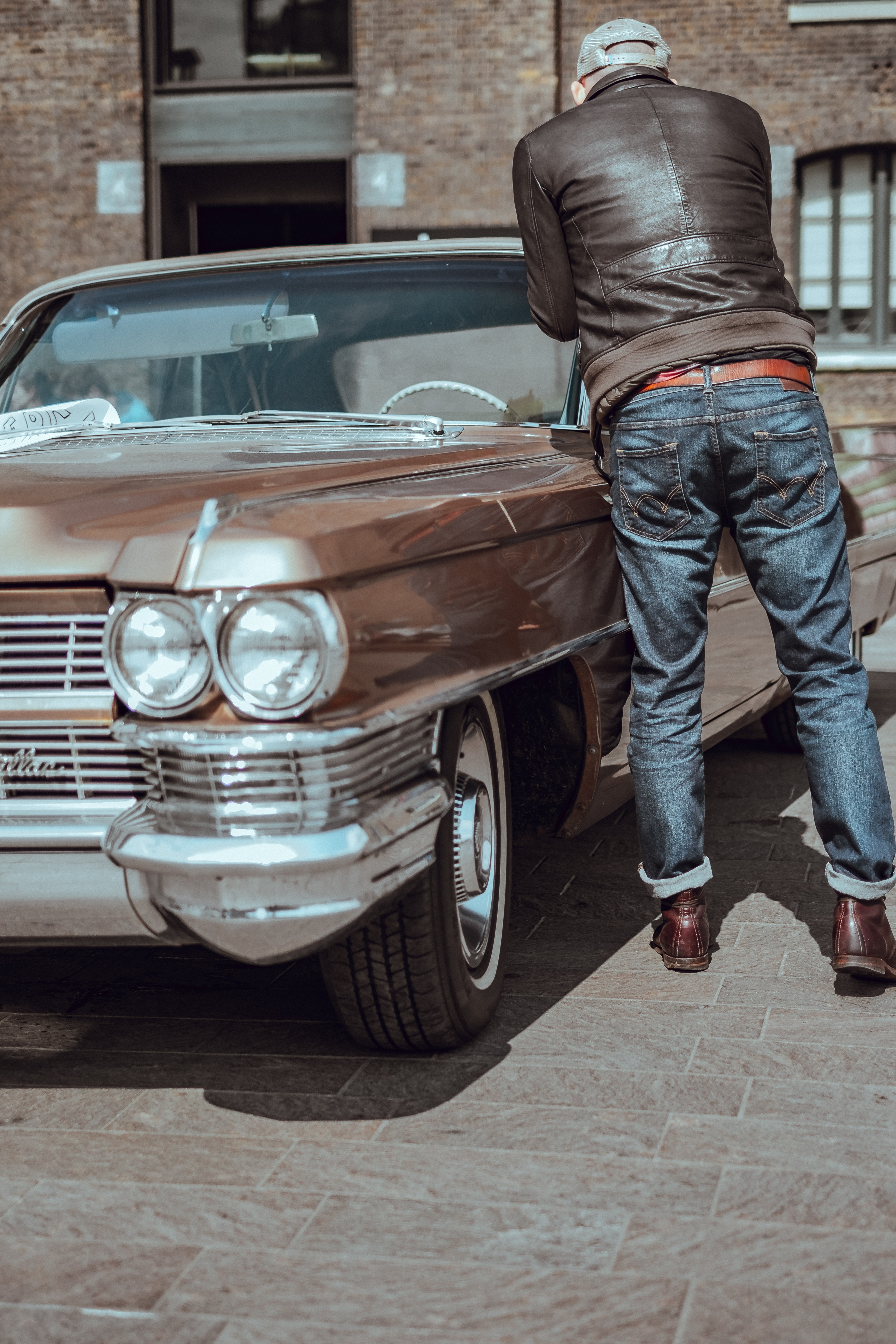 man in blue denim pants standing beside brown car