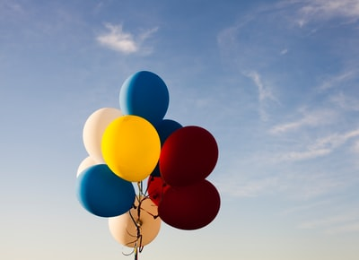 white, yellow, red, and blue balloons under blue sky balloons teams background