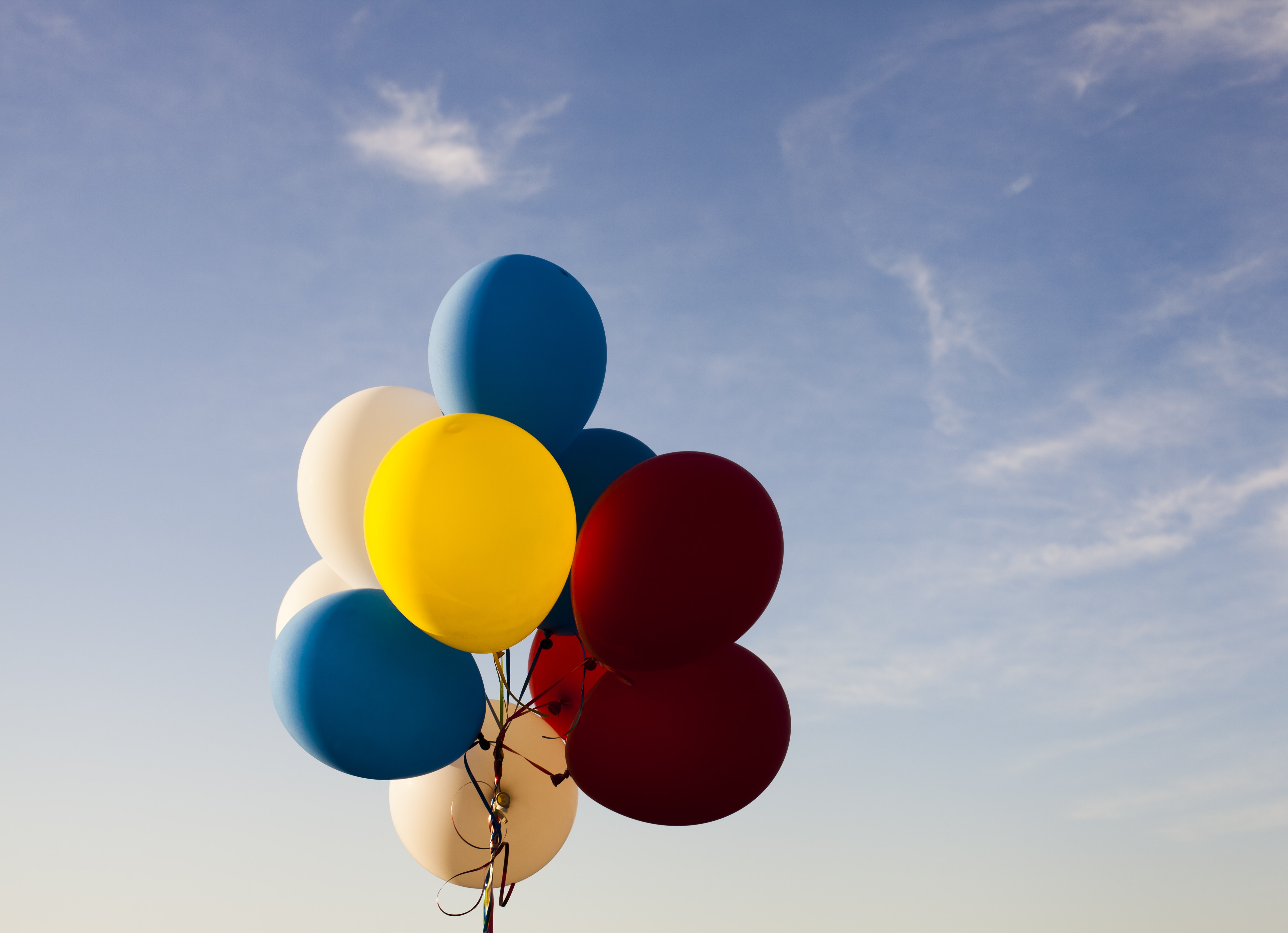 Colorful balloons on a string against a blue sky