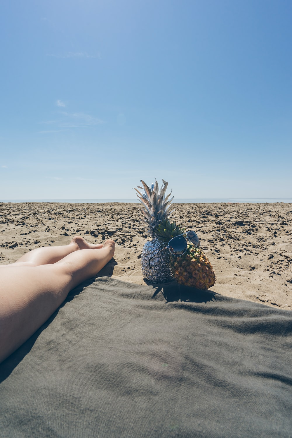 two pineapple near barefooted person on brown field