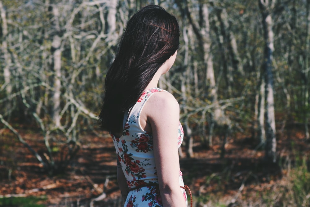 woman looking towards forest during daytime