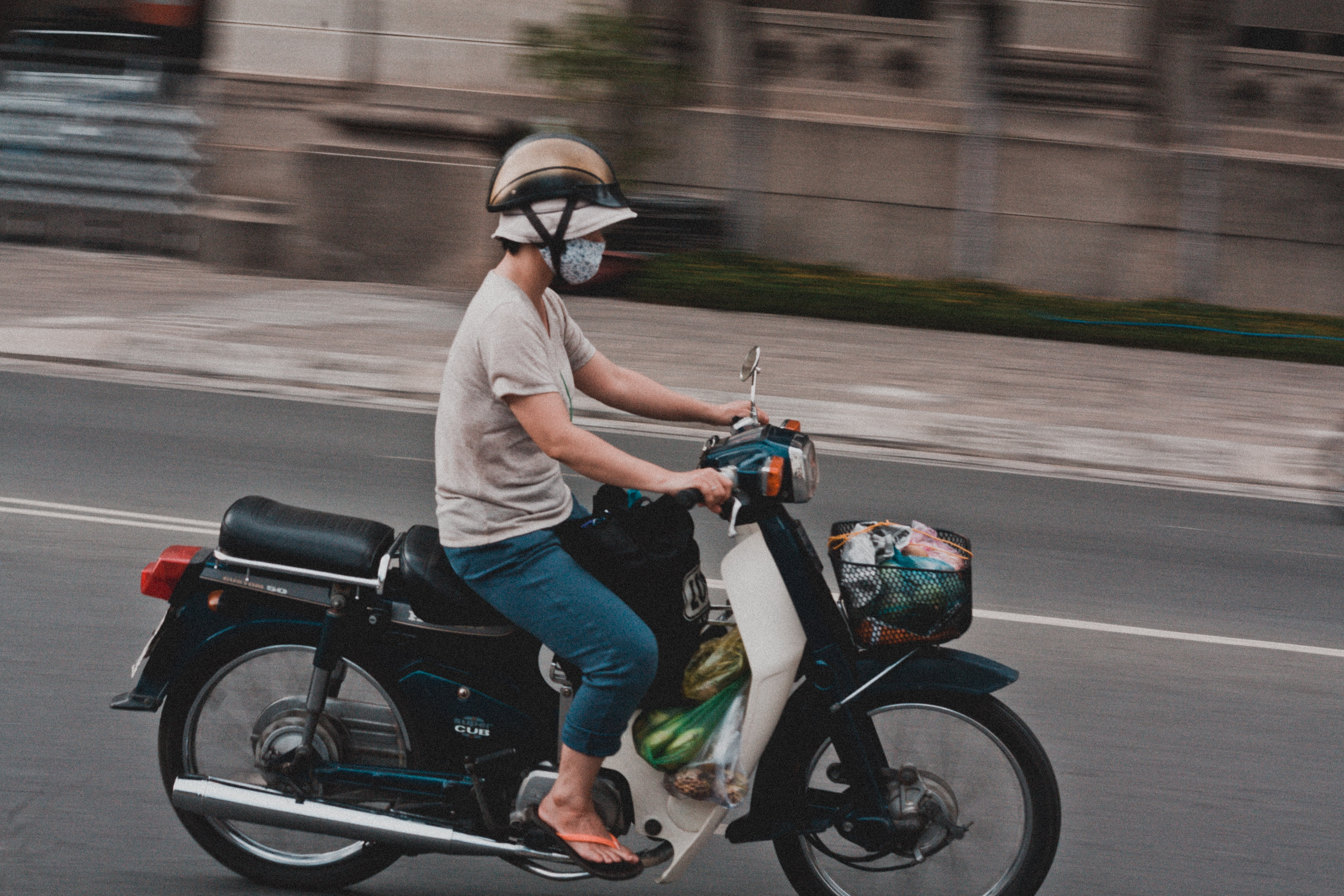 Man riding a motorcycle with grocery plastic bags while wearing a mouth mask and a hat