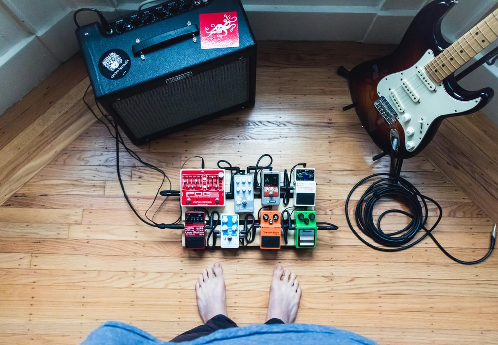 assorted guitar pedal lot beside electric guitar and amplifie