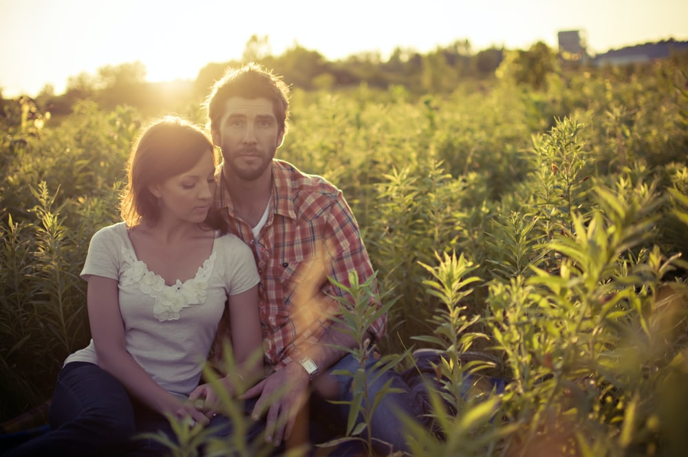 man and woman sitting on grass field at daytime