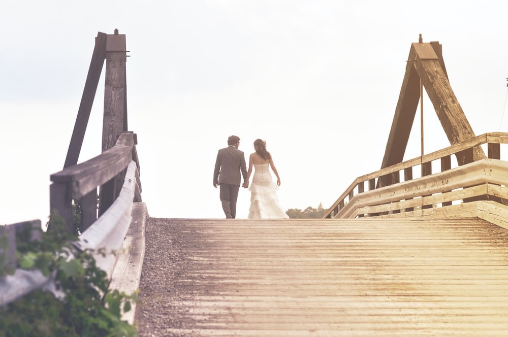 wedding couple walking on the middle of wooden bridge