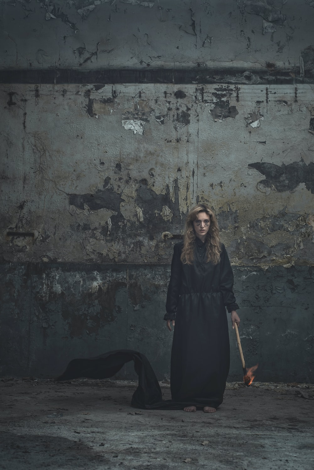 woman in black dress standing in front of gray wall