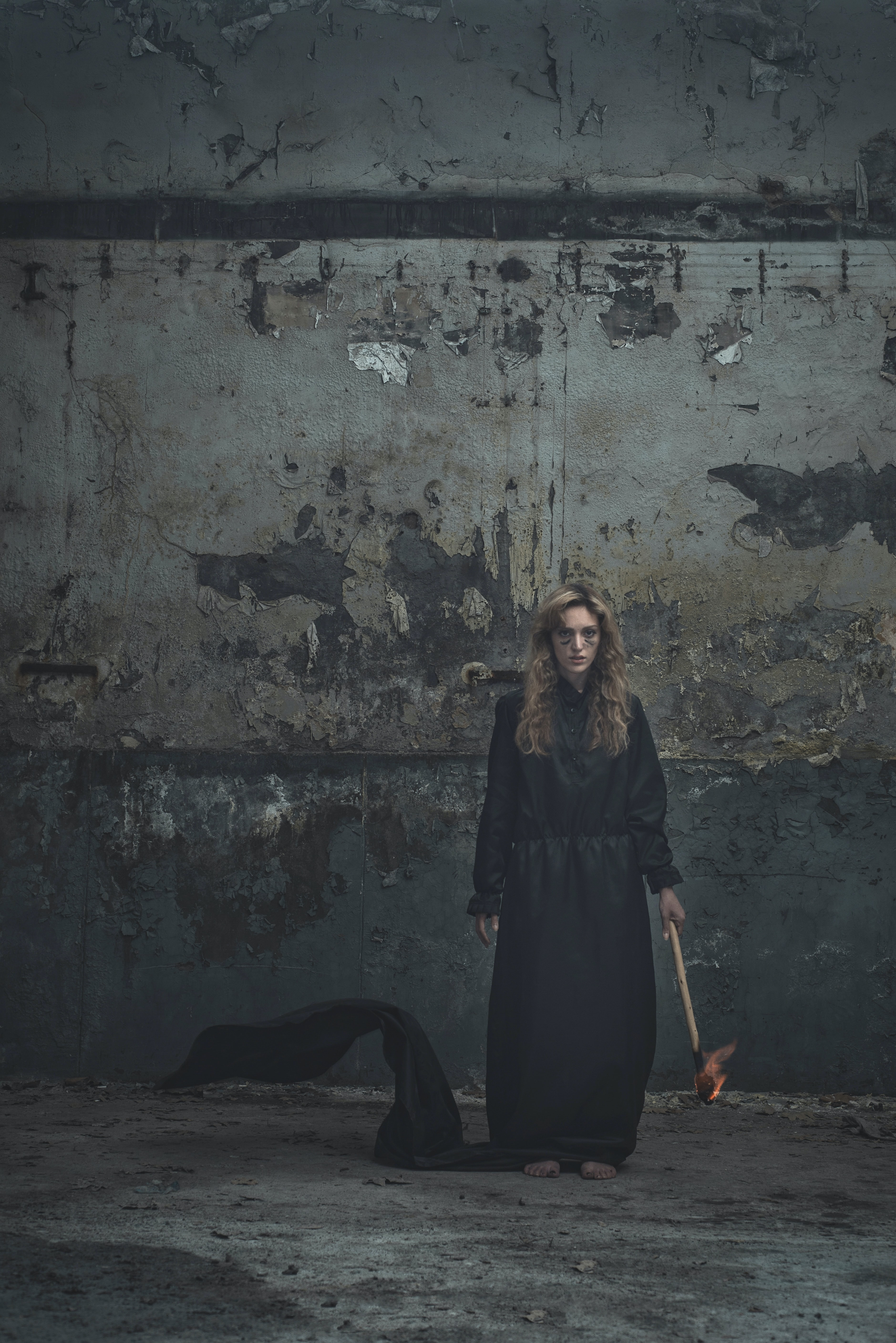 A woman in a long black dress holds a lit torch beside a dirty gray wall