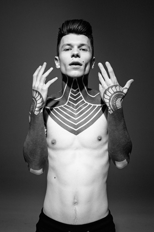 man standing showing black tattoo