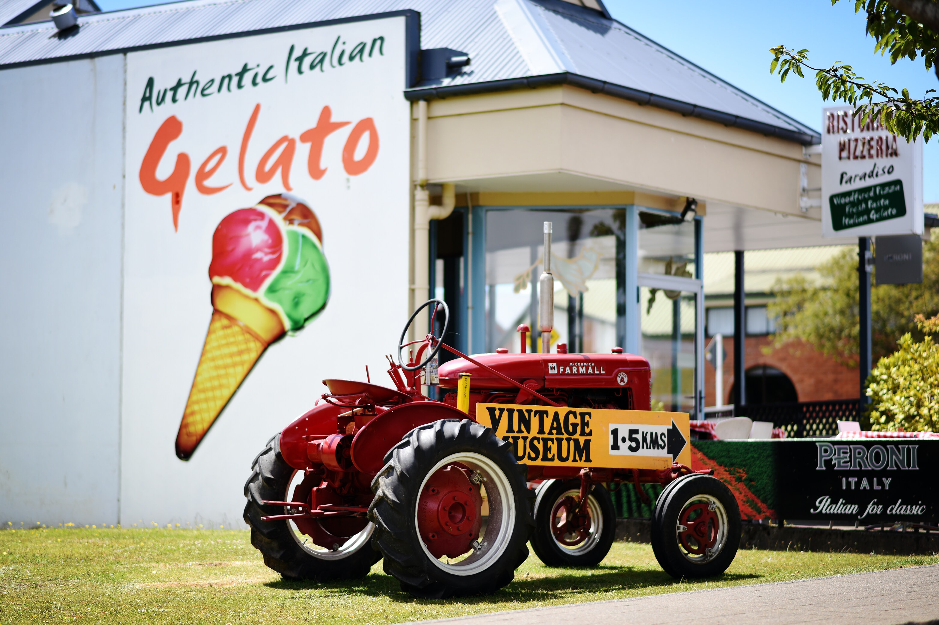 A vintage tractor sitting outside of a Gelato shop in New Zealand