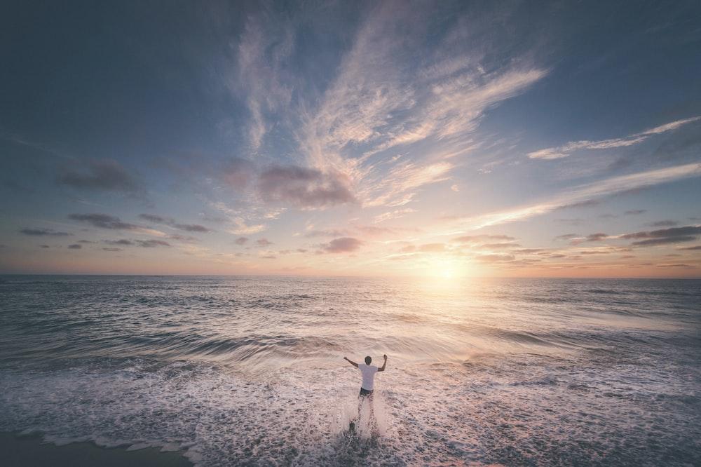 man standing on seashore during sunset