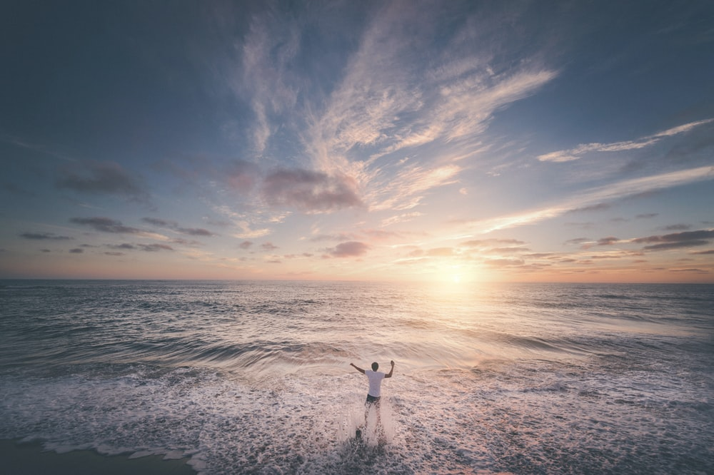 man standing on seashore during sunset