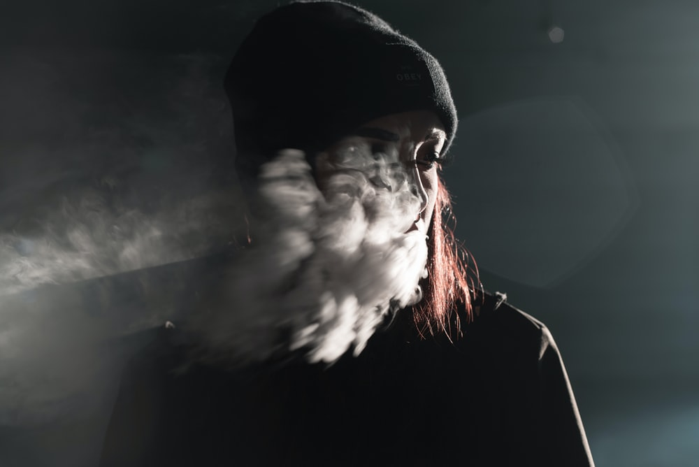 portrait photography of person blowing smoke