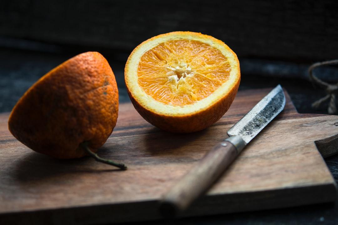 Fresh orange slice in half on a rustic cutting board