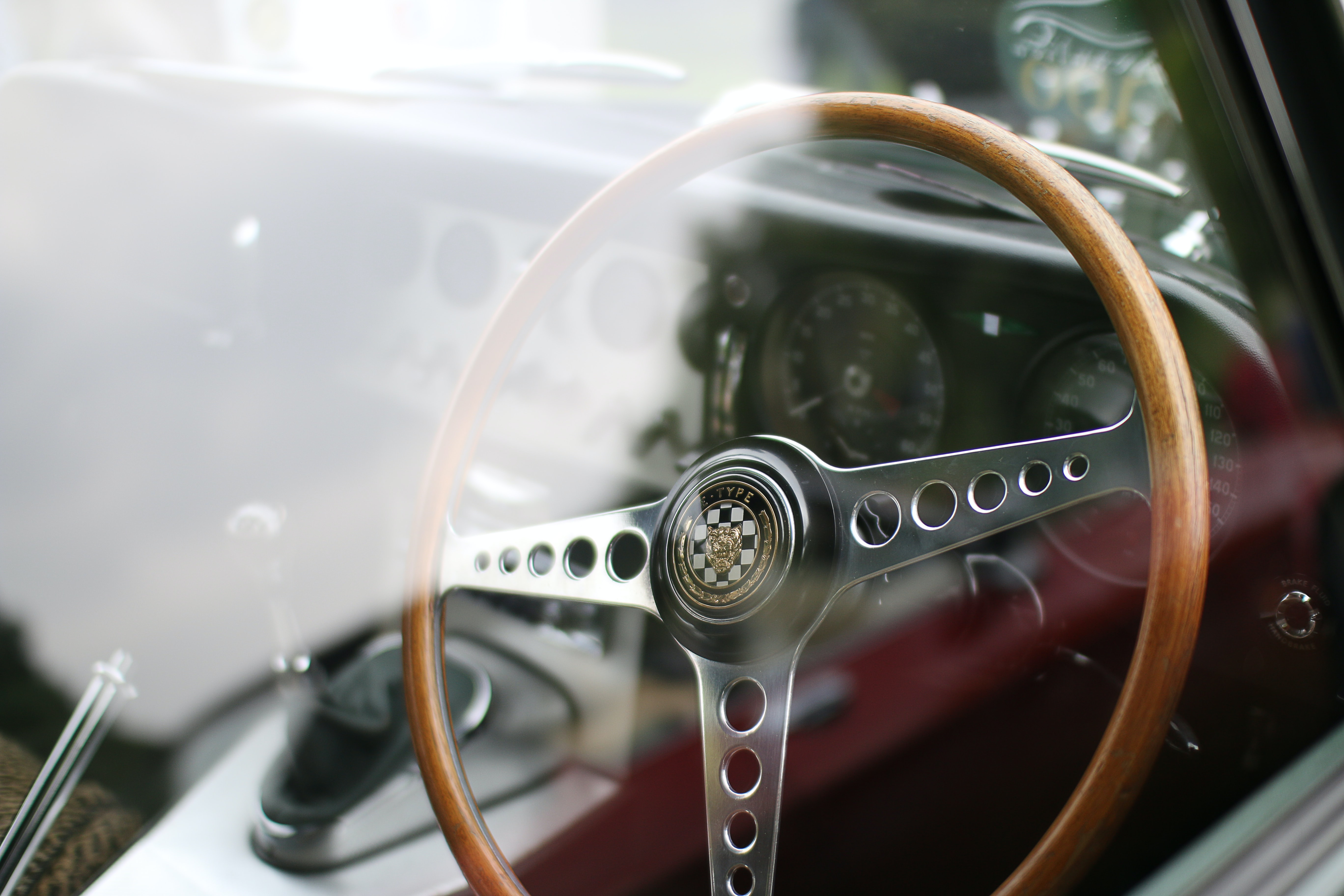 Interior of vintage car with wooden steering wheel from outside of window with reflection, Windsor