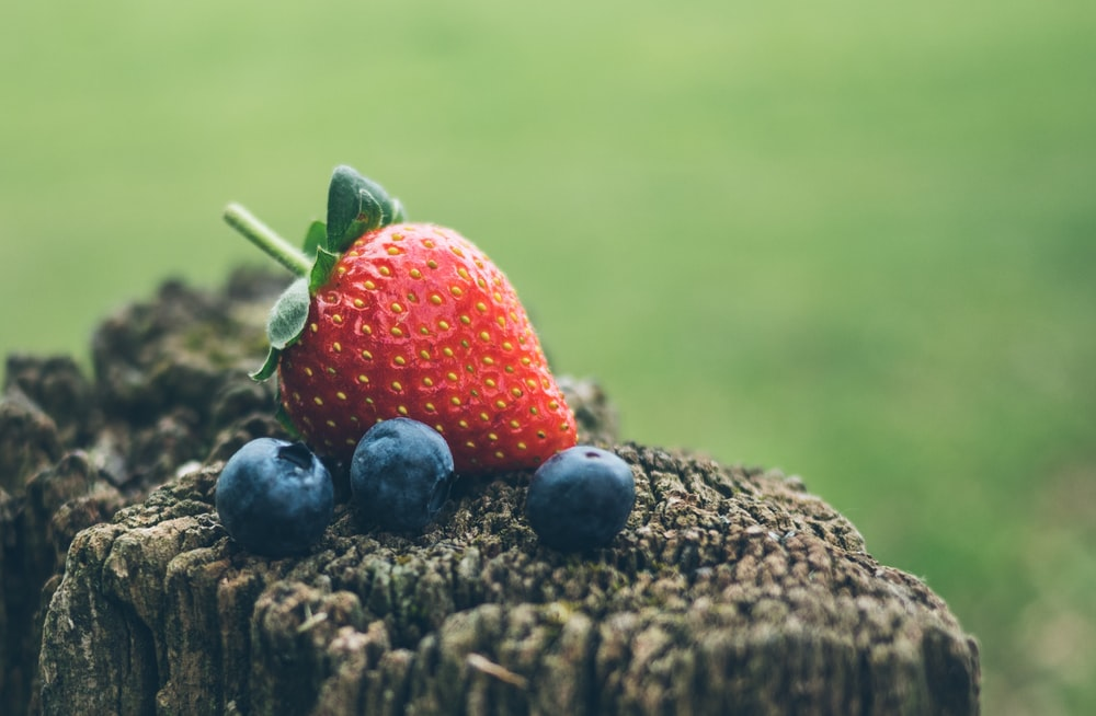 strawberry and three blueberries in closeup photography