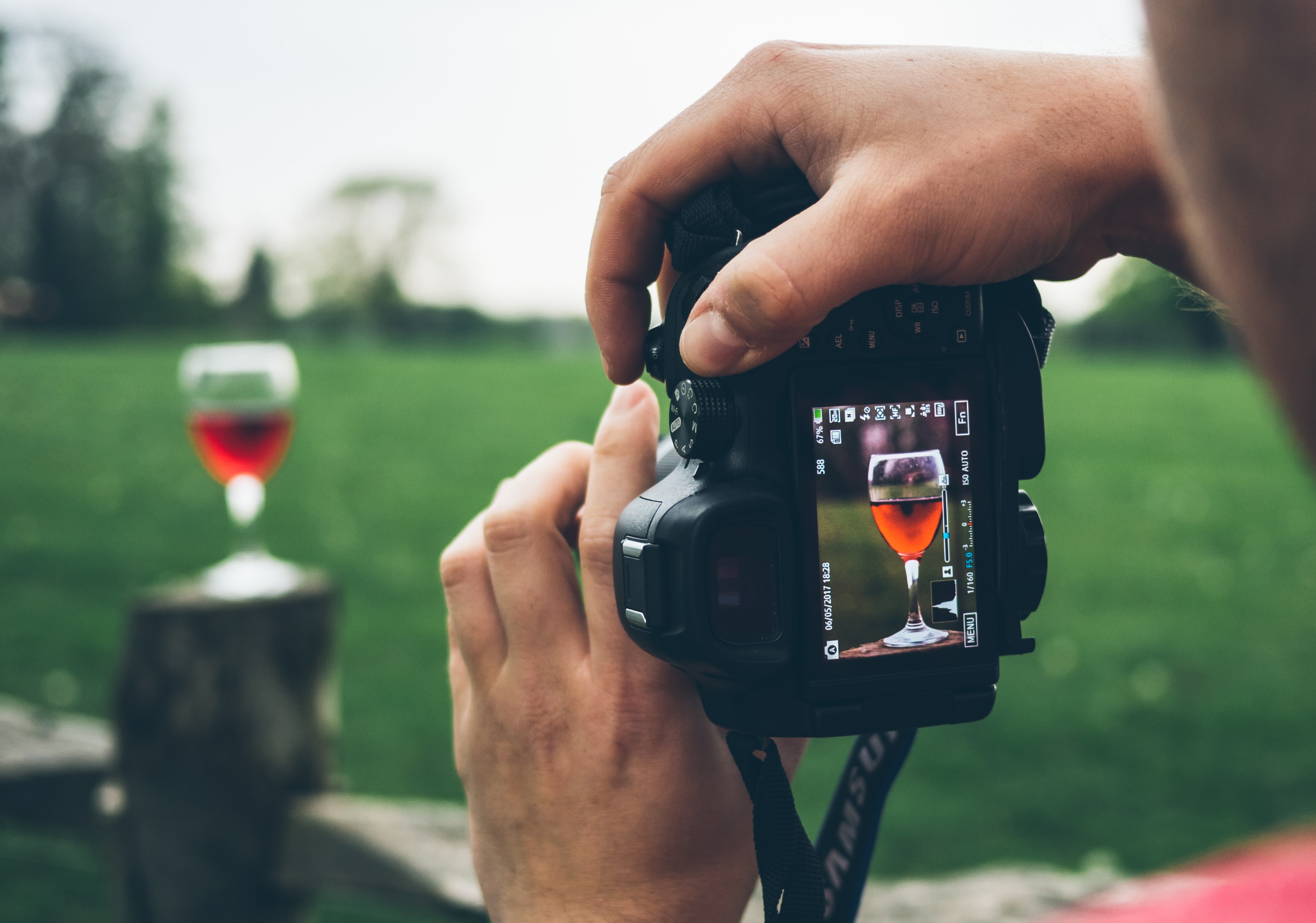 person taking photo of wine goblet