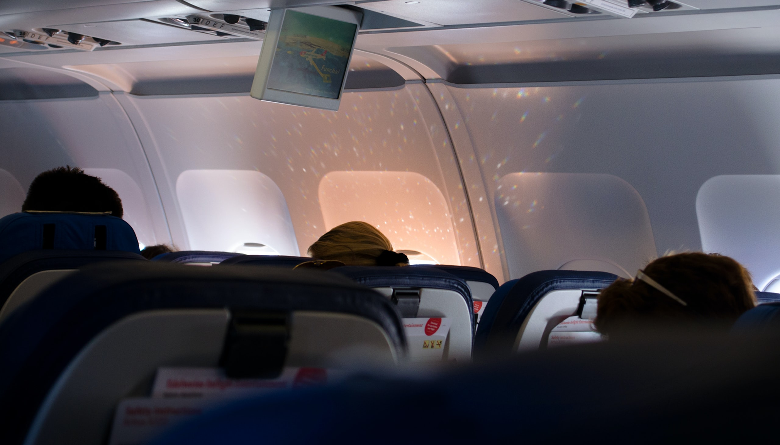 Interior shot of a plane focused on the back of a person sitting by the window illuminating the wall with reflected light