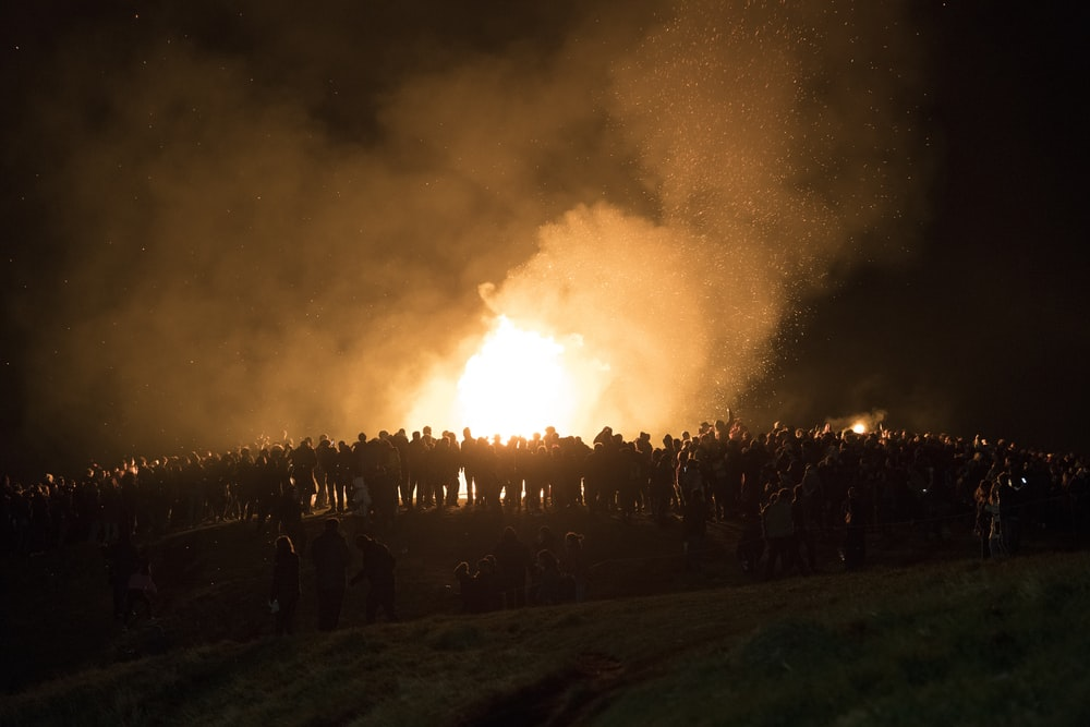 people gathered near bonfire during nighttime