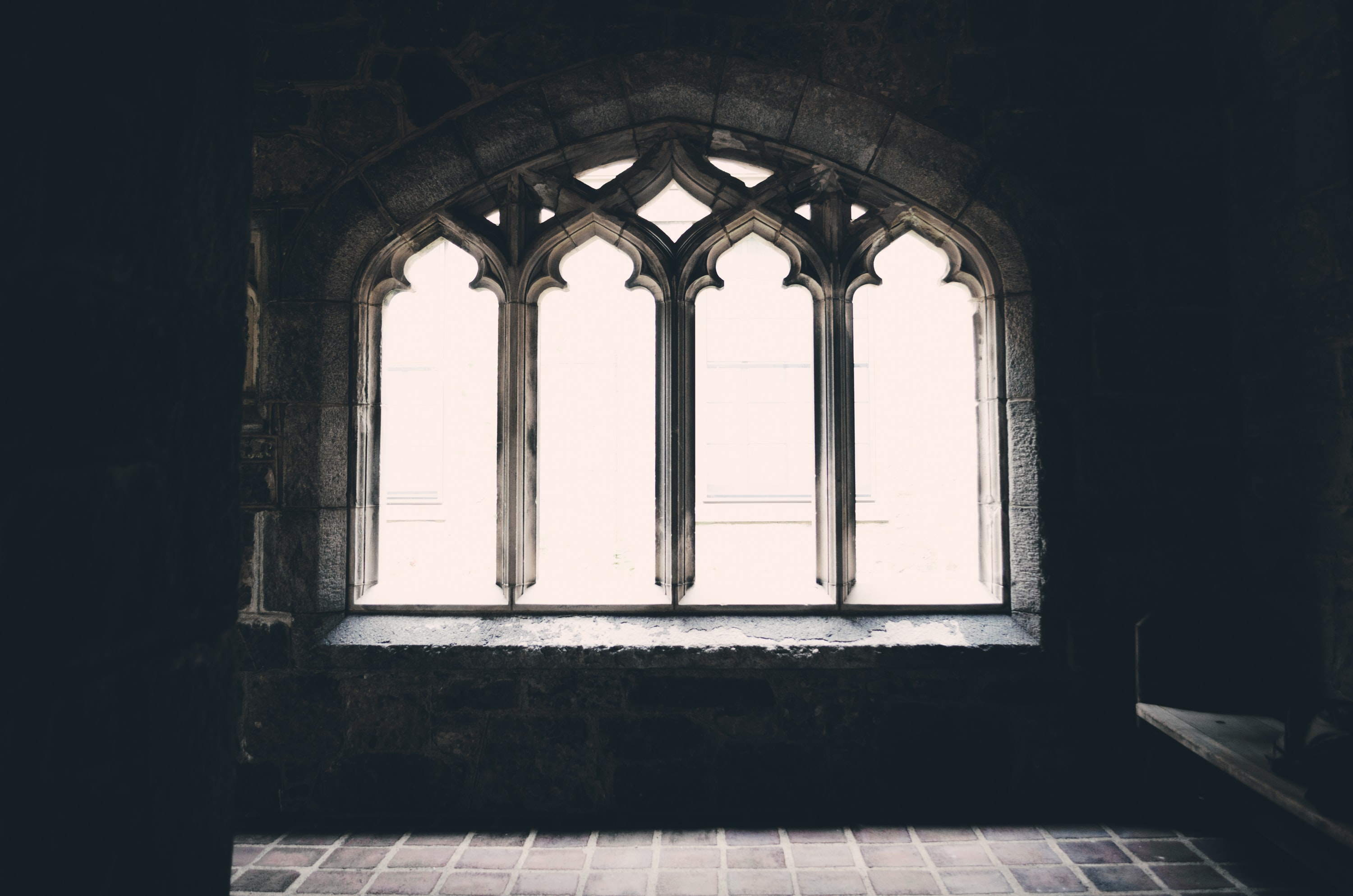 A darkened picture capturing a window inside of a church.