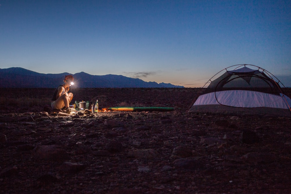 person camping beside white and black tent