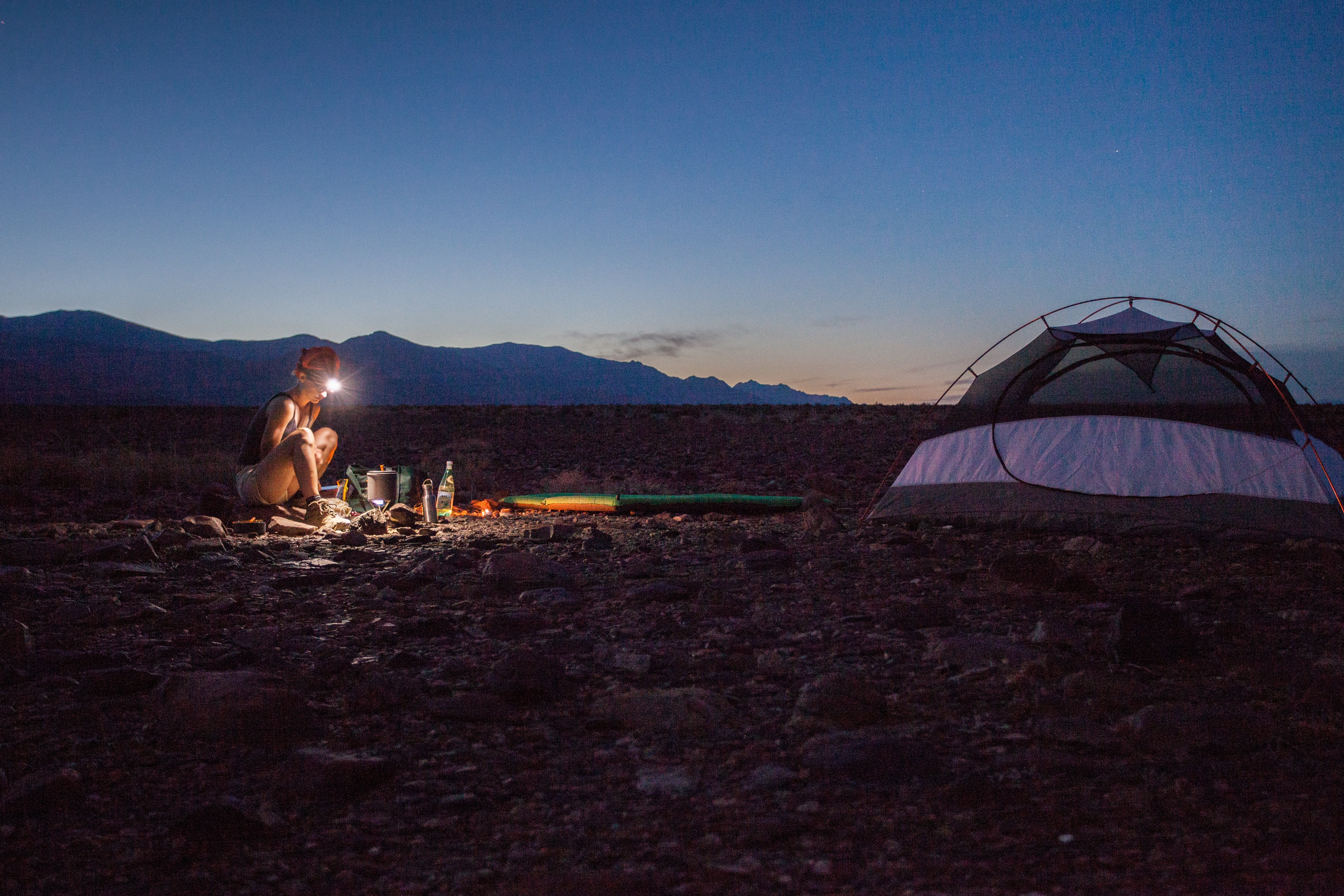 A lone woman c&ing on a rocky plain in the Death Valley in the evening & Tent Pictures | Download Free Images on Unsplash