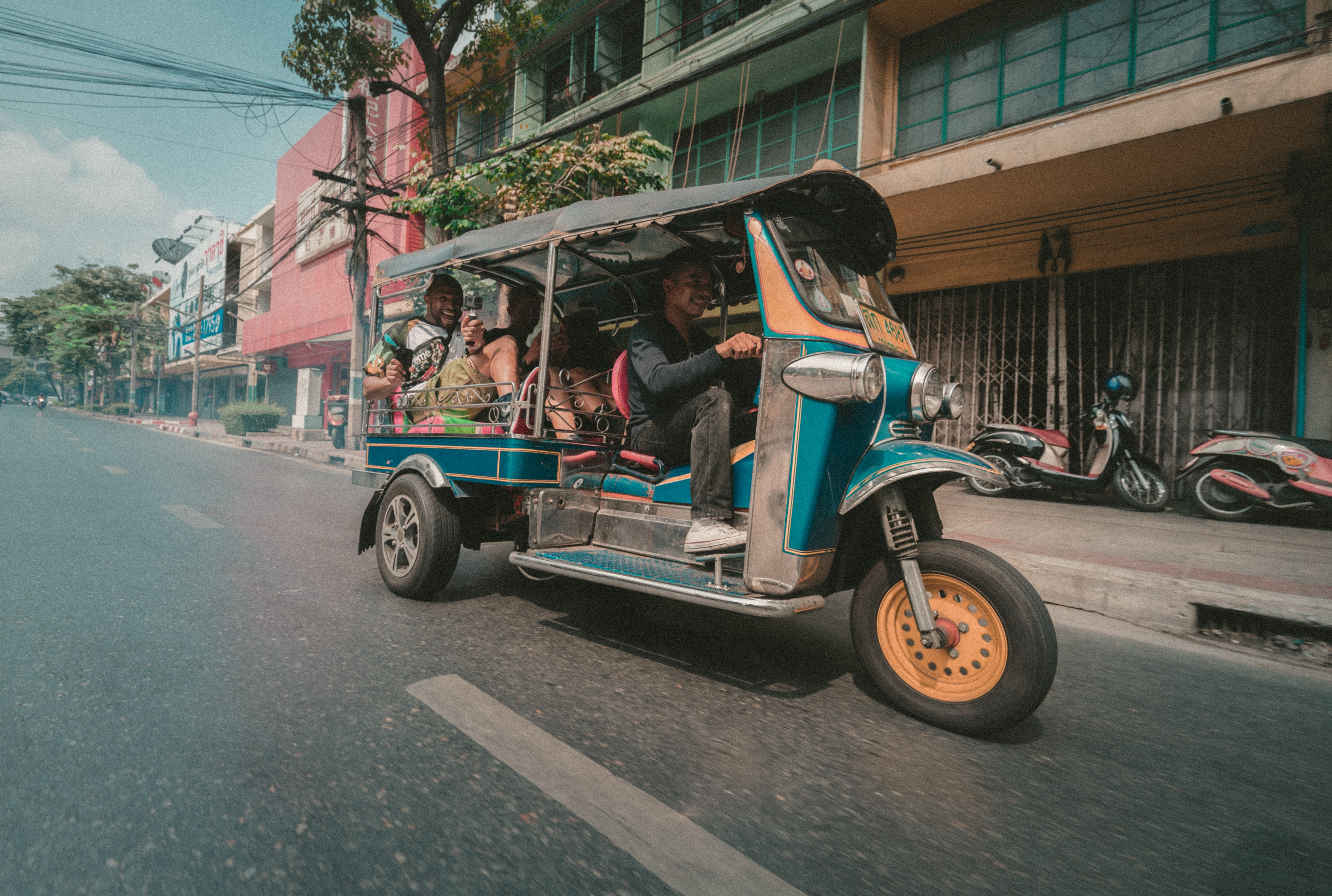 Small colorful taxi with several passengers drives down the street near buildings in Bangkok