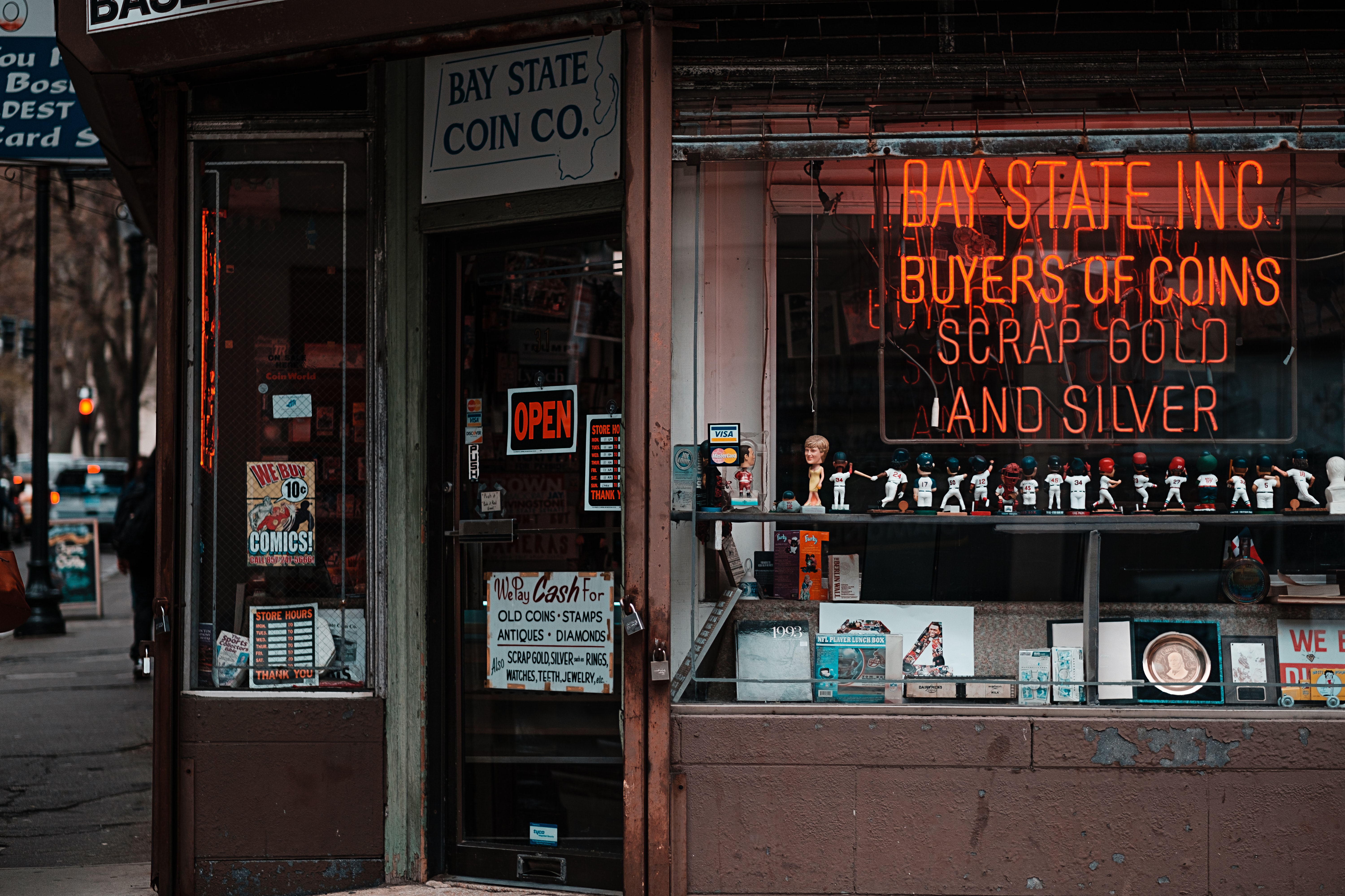 A coin and antique buyer storefront with a neon sign