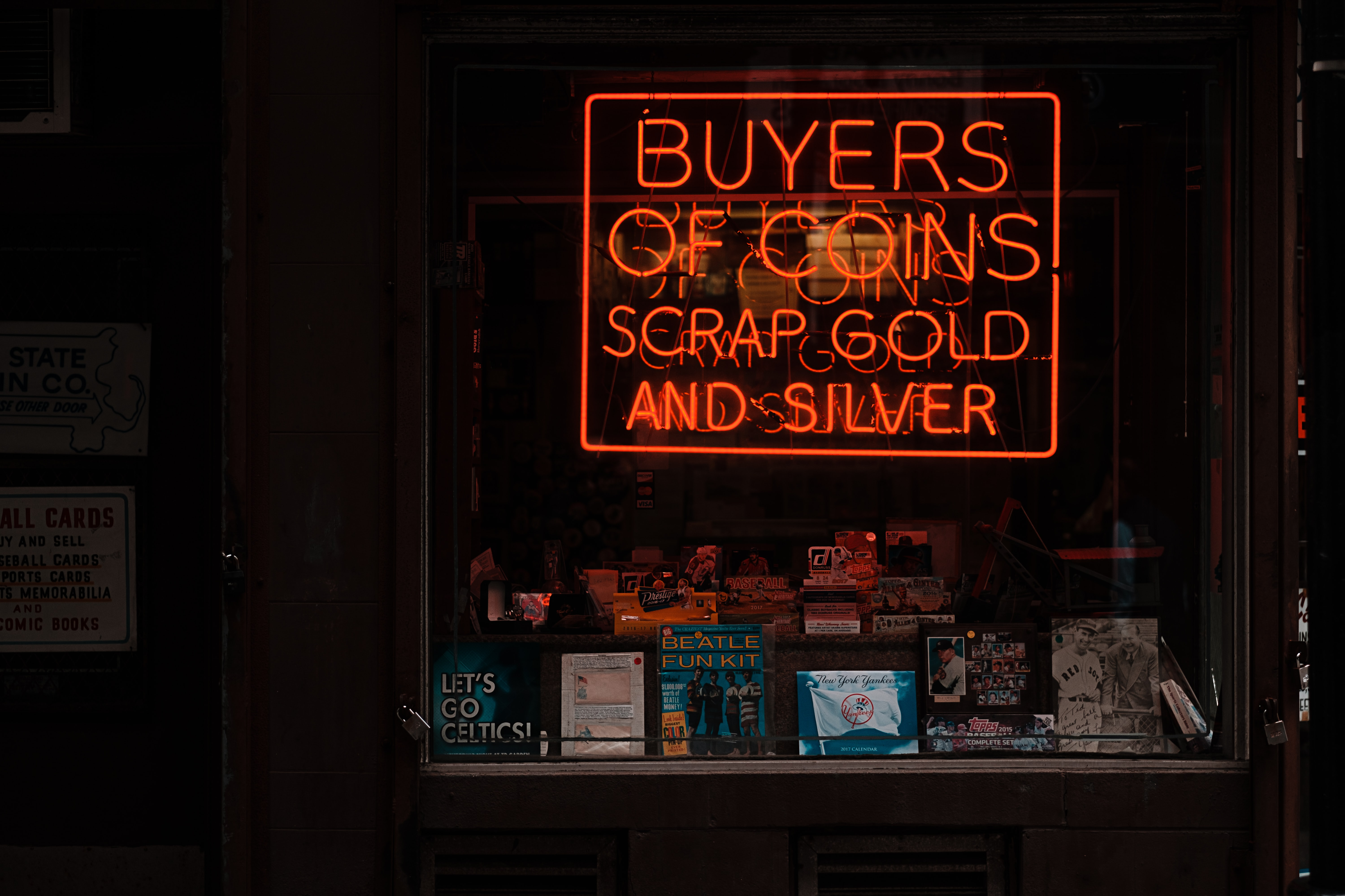 Red neon sign reading Buyers of Coins above stacks of books and photos in window display