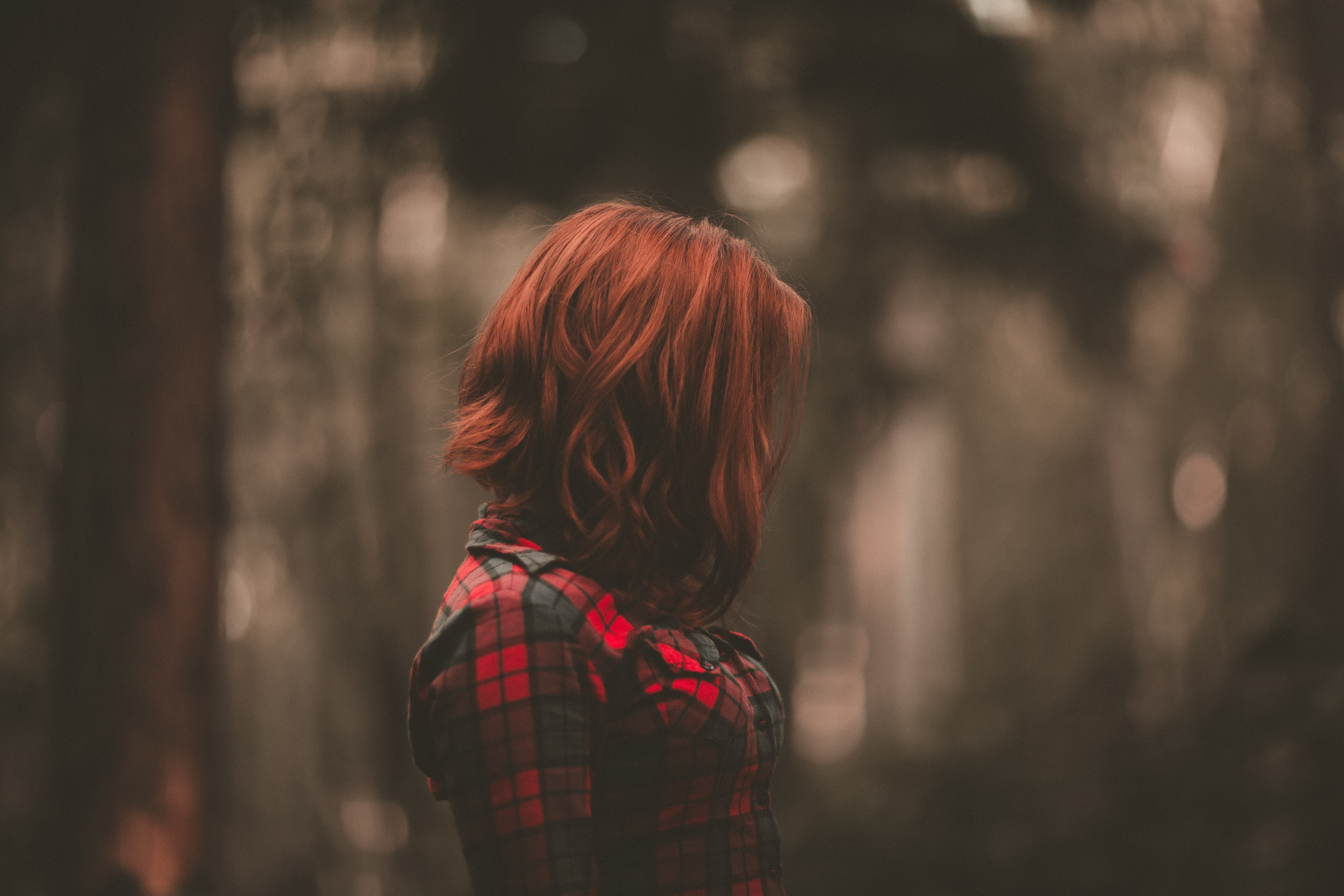 A woman with red hair obscuring her face in a plaid shirt against a blurry background