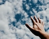 person hand reaching for the sky