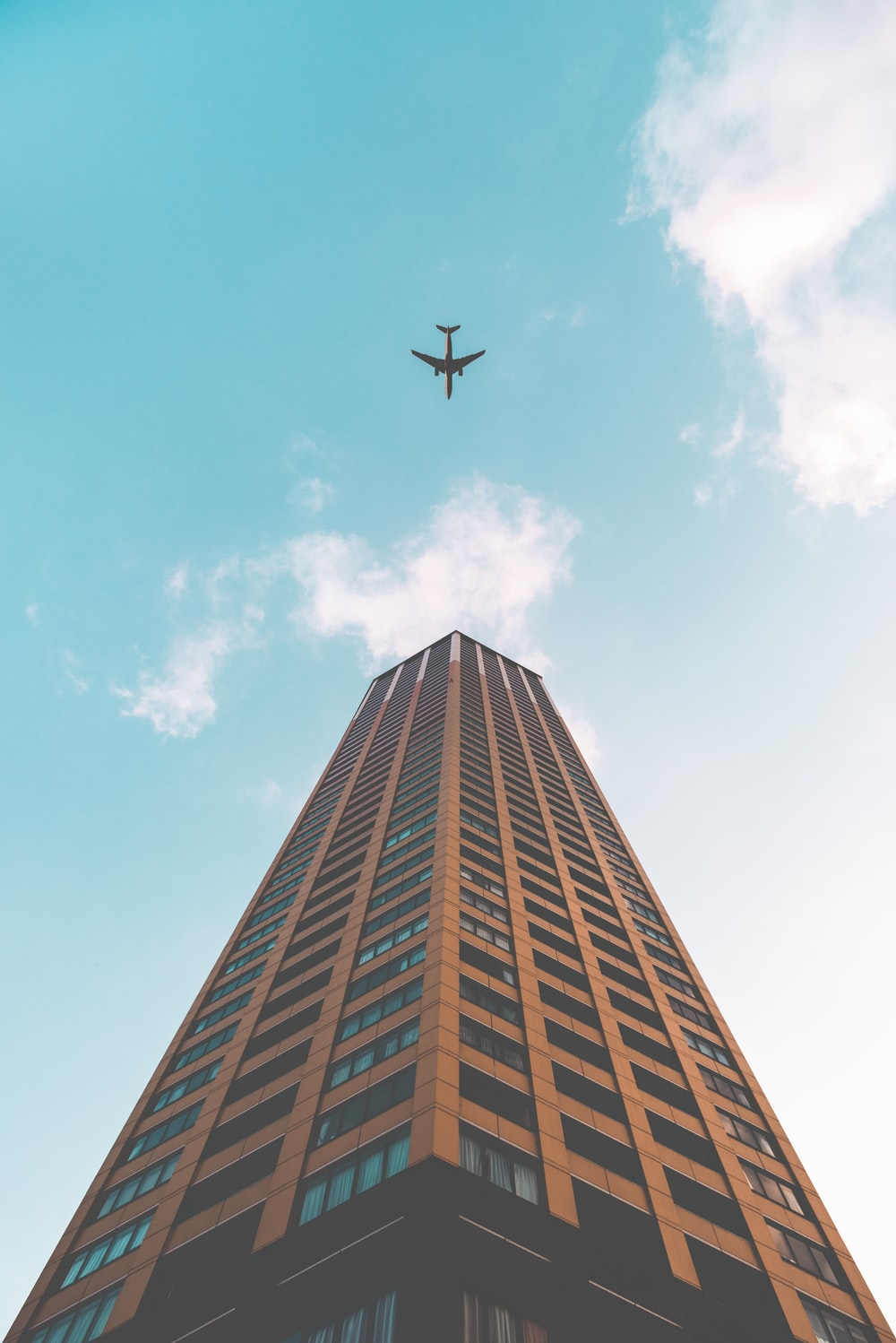 bottom view shot of airplane flying above high rise building