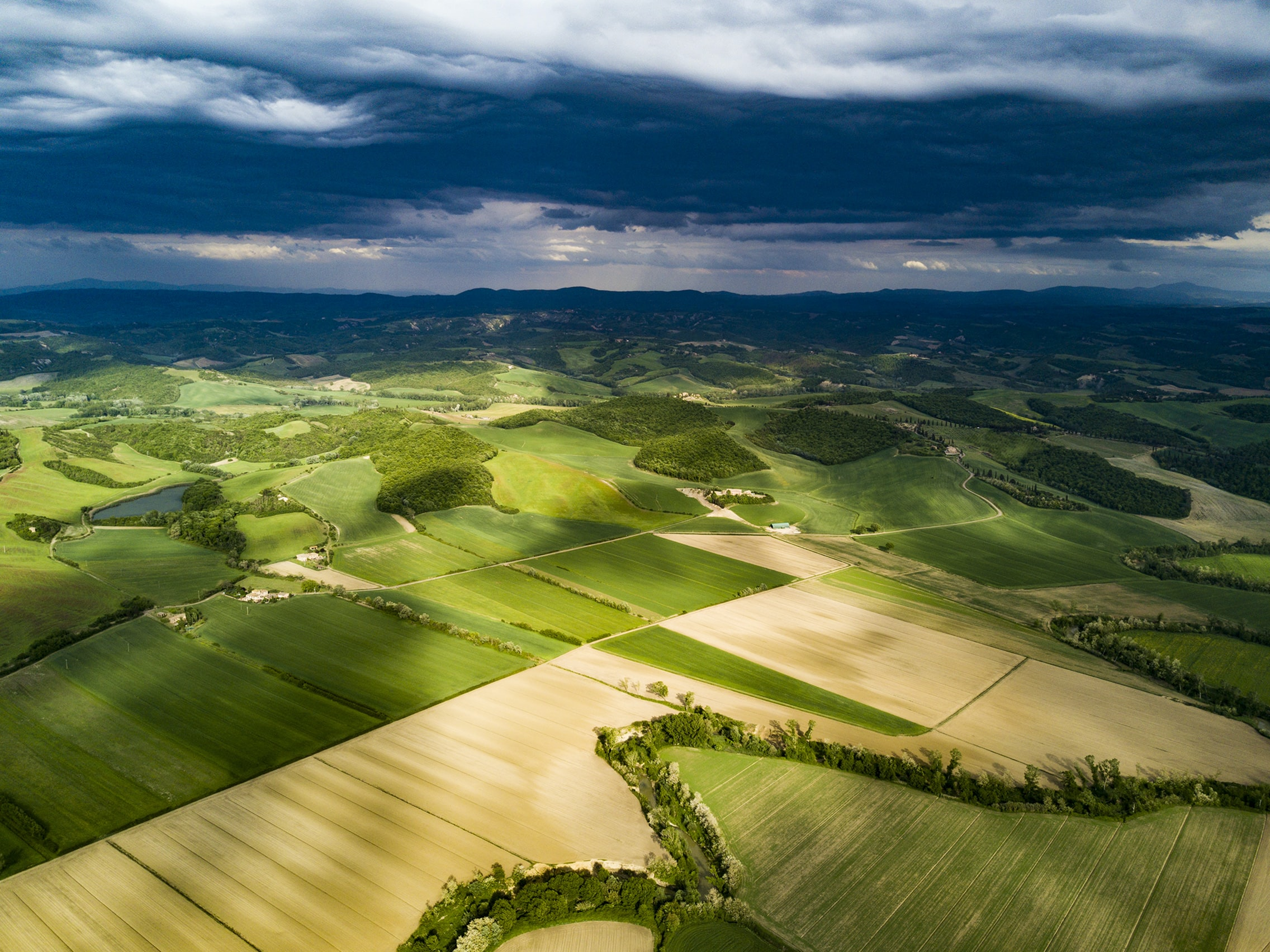 A drone shot of a patchwork of green fields in Tuscany