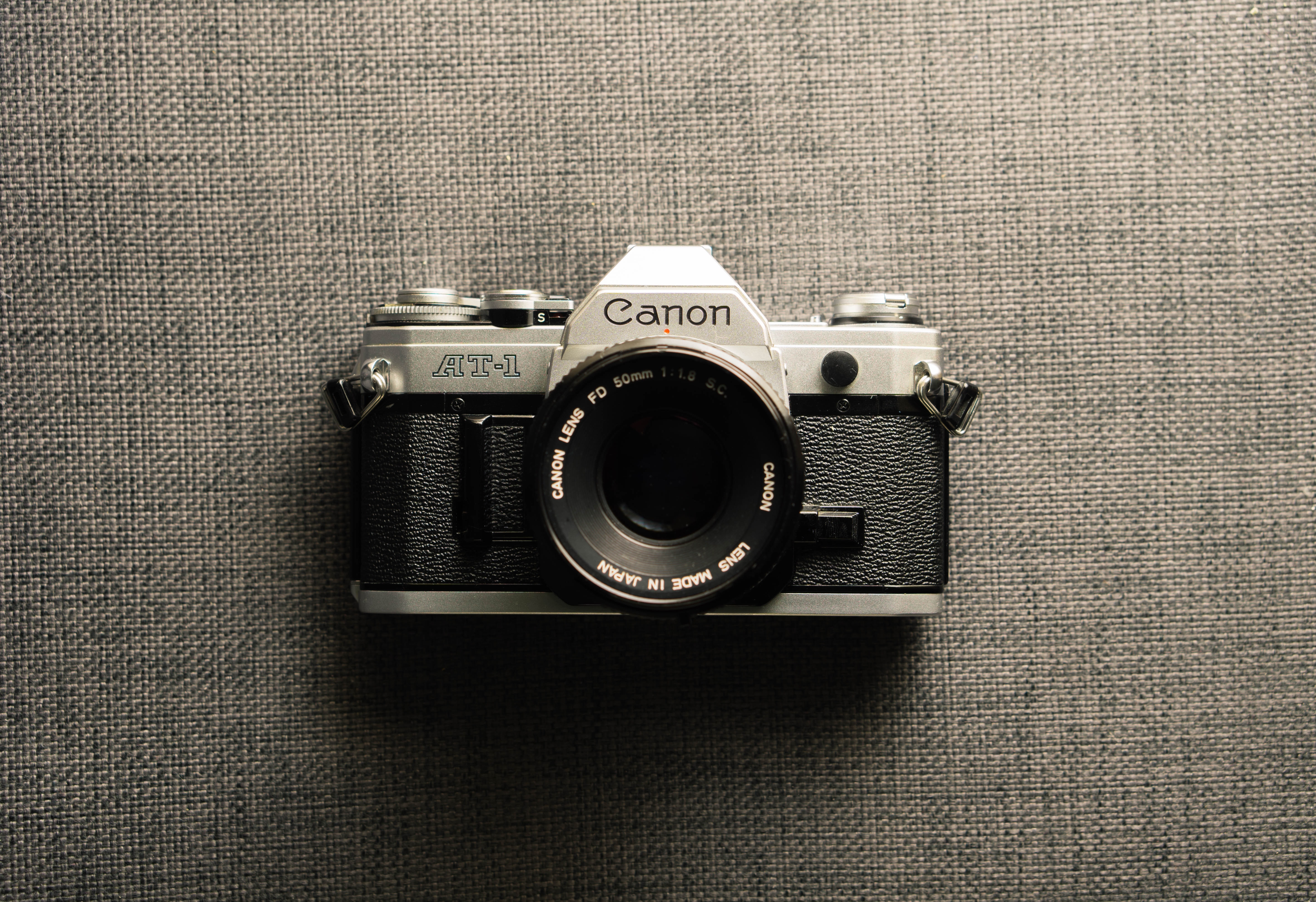 Canon AT-1 vintage camera on a gray fabric