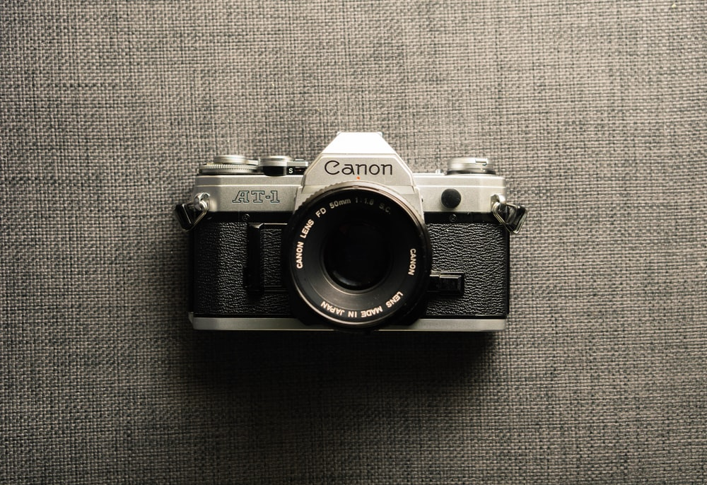 black and gray Canon camera on gray textile