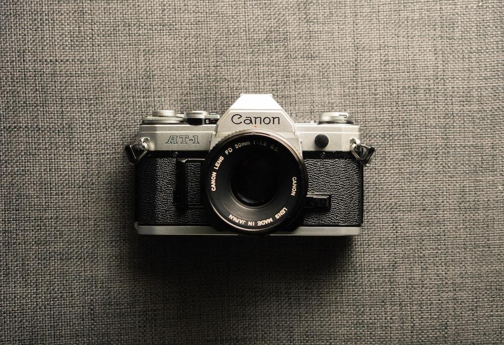 black and gray Canon camera on gray textile