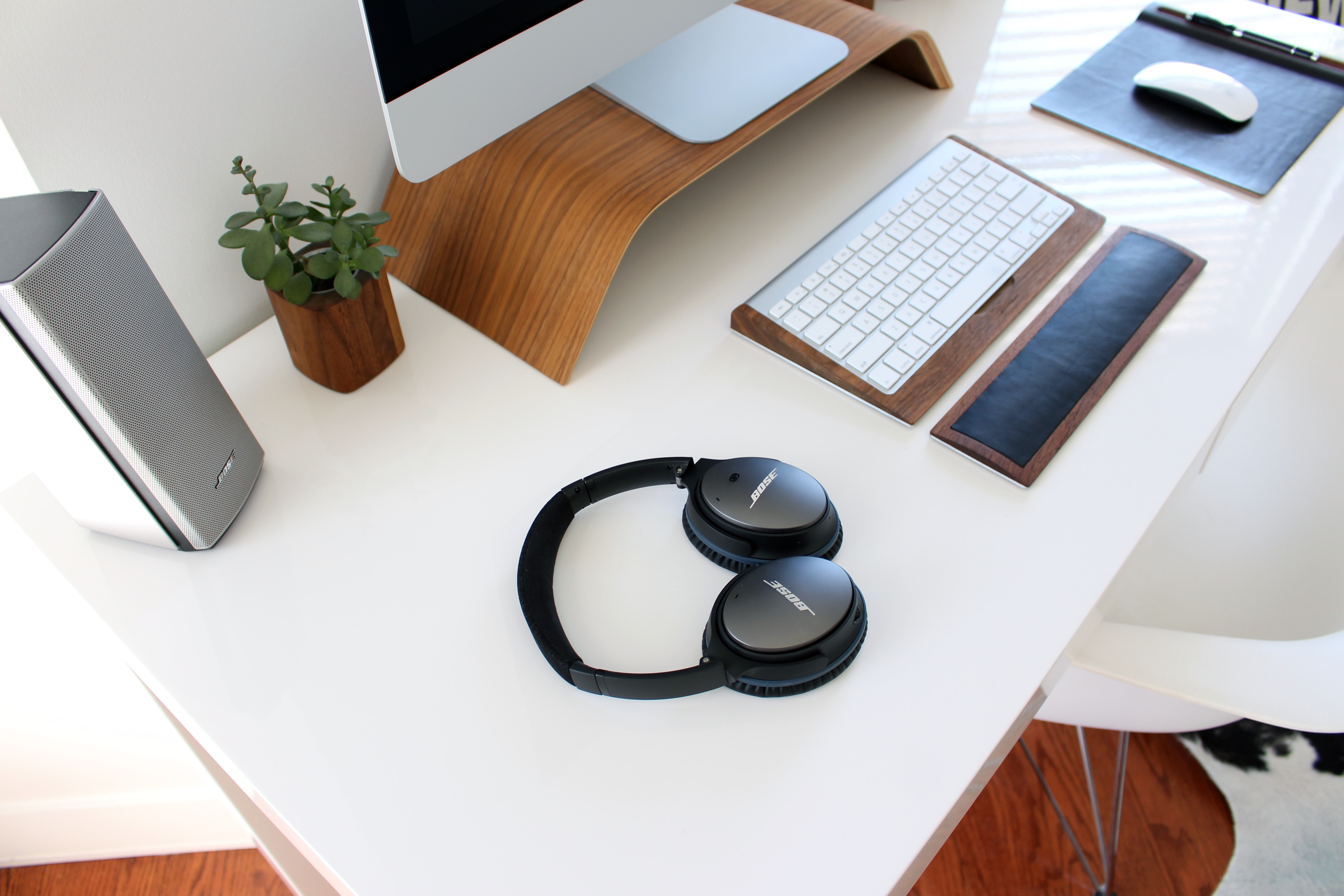 A desk with headphones, a keyboard and wrist wrest, monitor, mouse, speakers and a plant.