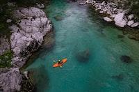 person on riding orange kayak on river