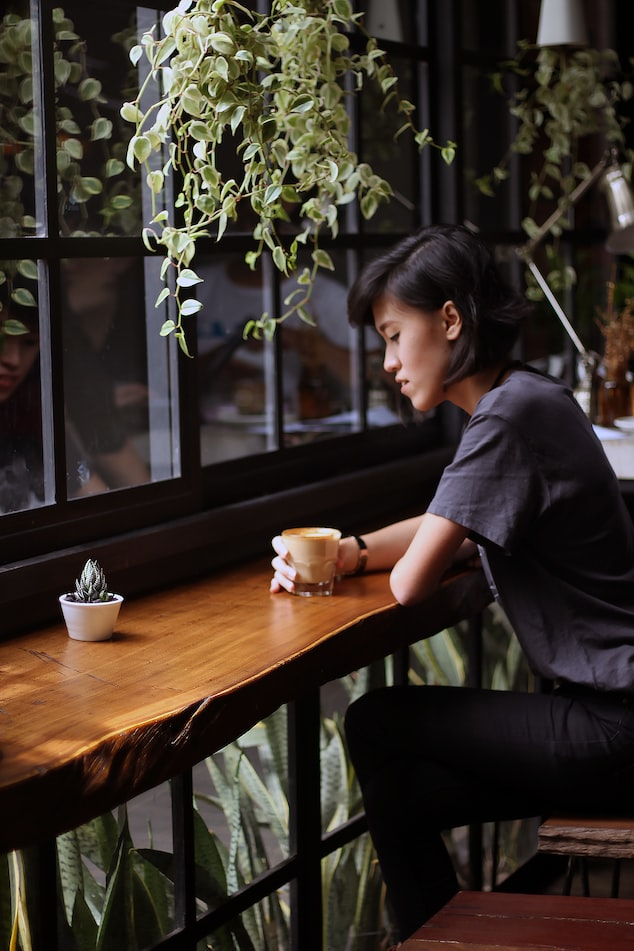 A photo of a woman sitting at a bar in a cafe, with a coffee cup, staring into space. She looks worried.