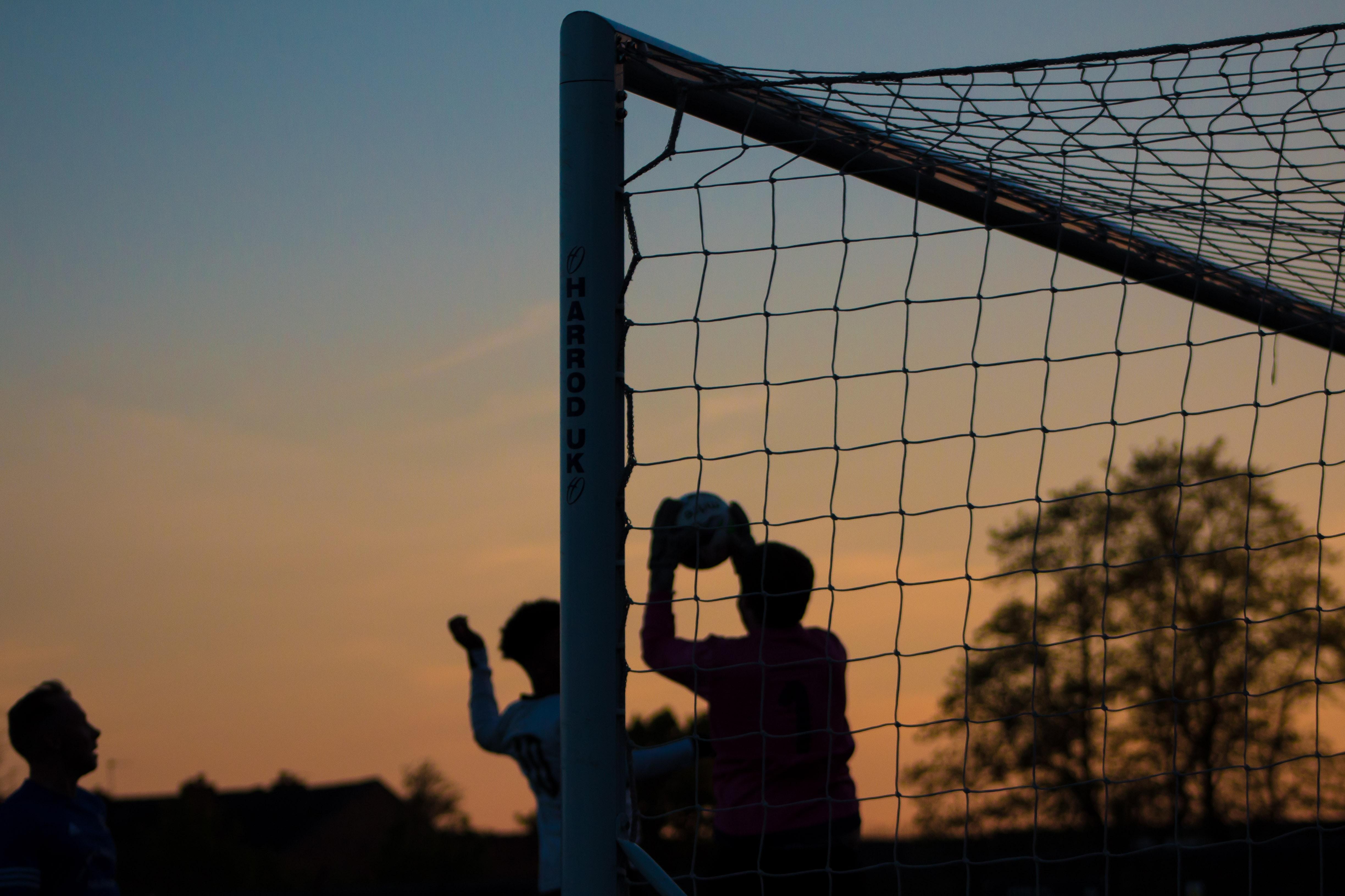 Three children play soccer at sunset at Ewen Fields