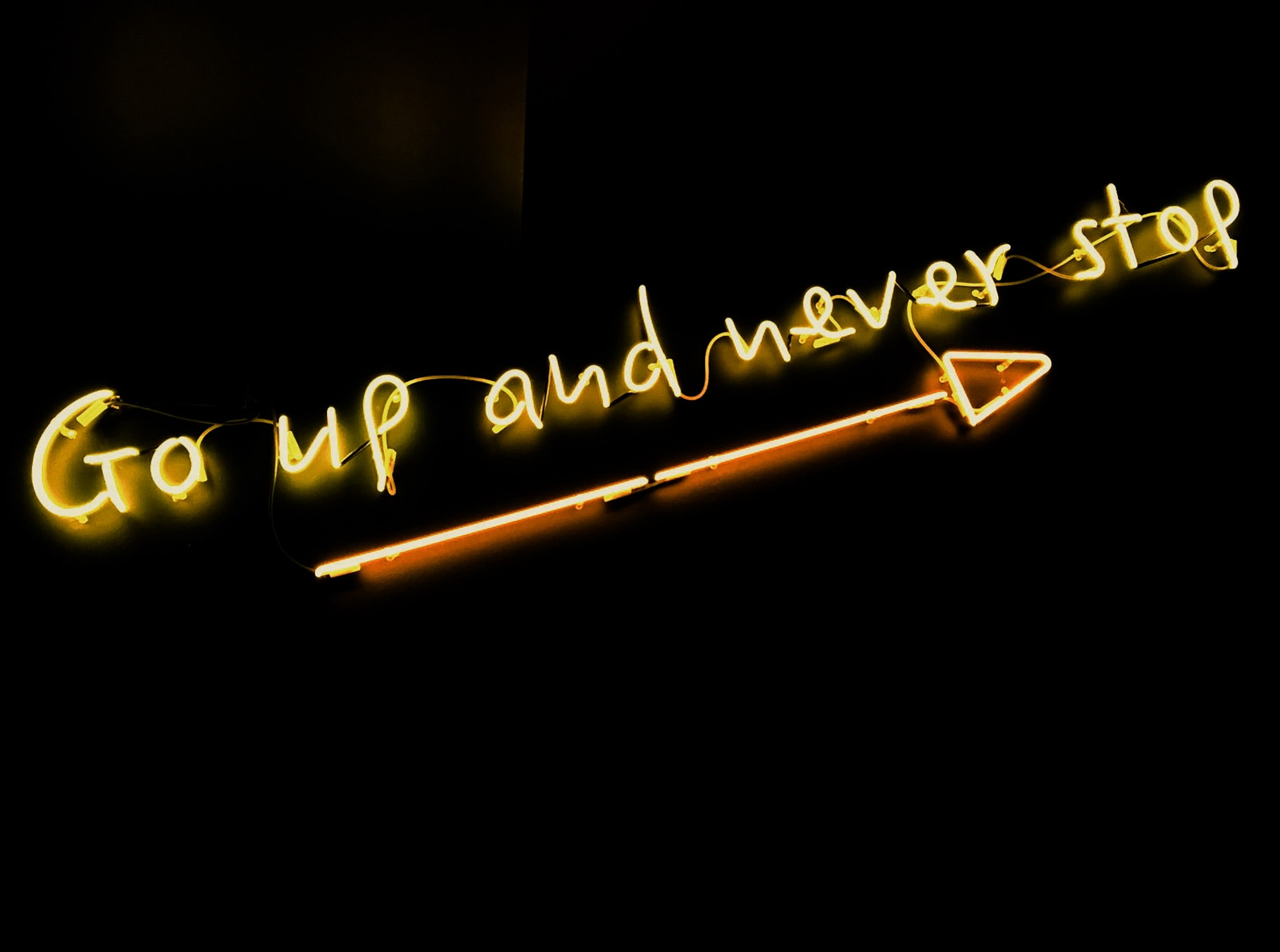 "A yellow ""Go up and never stop"" neon with a long arrow against a black background"