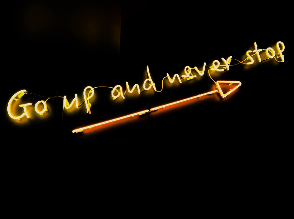 "Photograph of a neon sign on a black background that reads ""go up and never stop""."